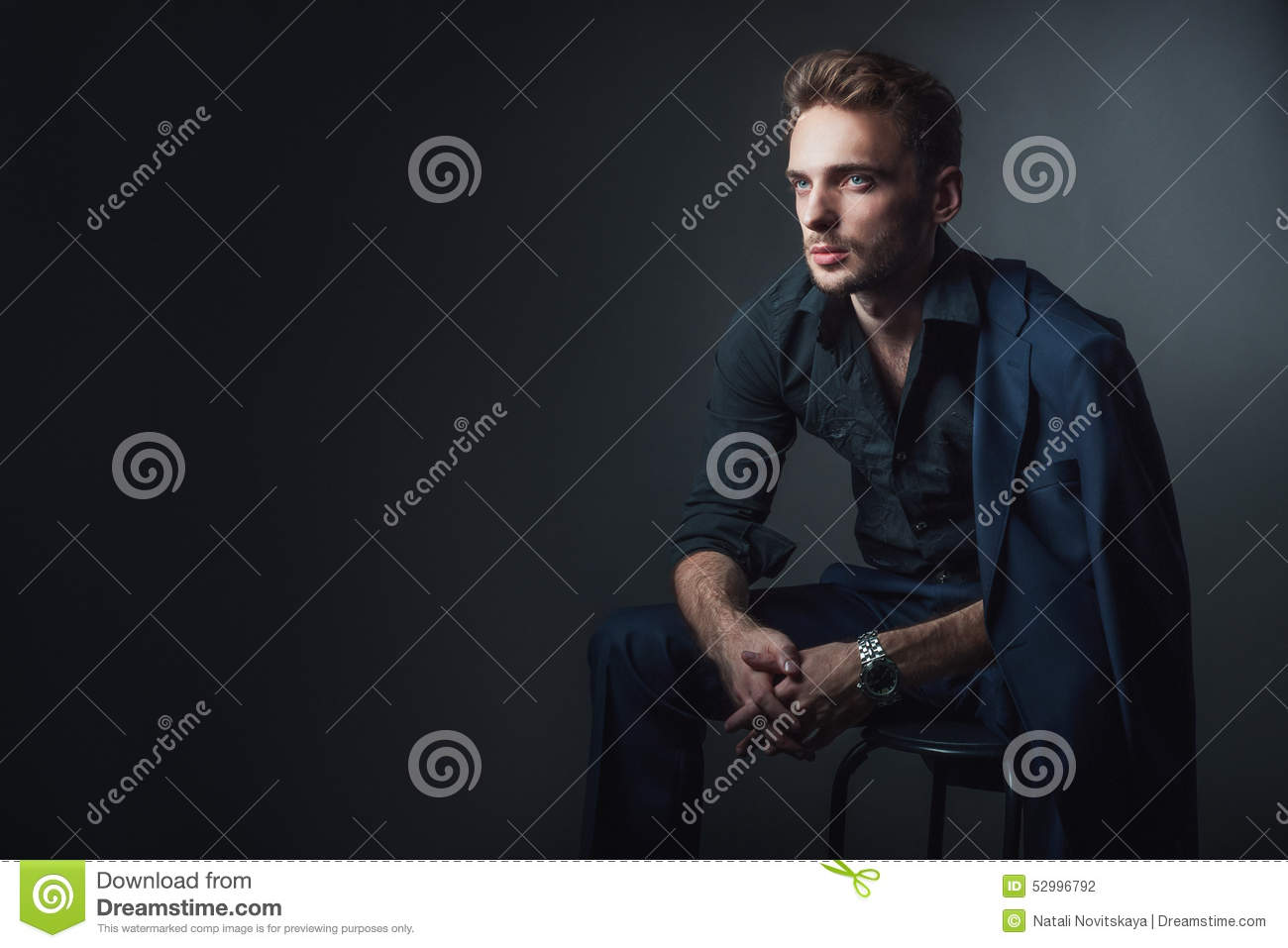 Young Man In A Classic Suit Sitting On A Chair Stock Photo
