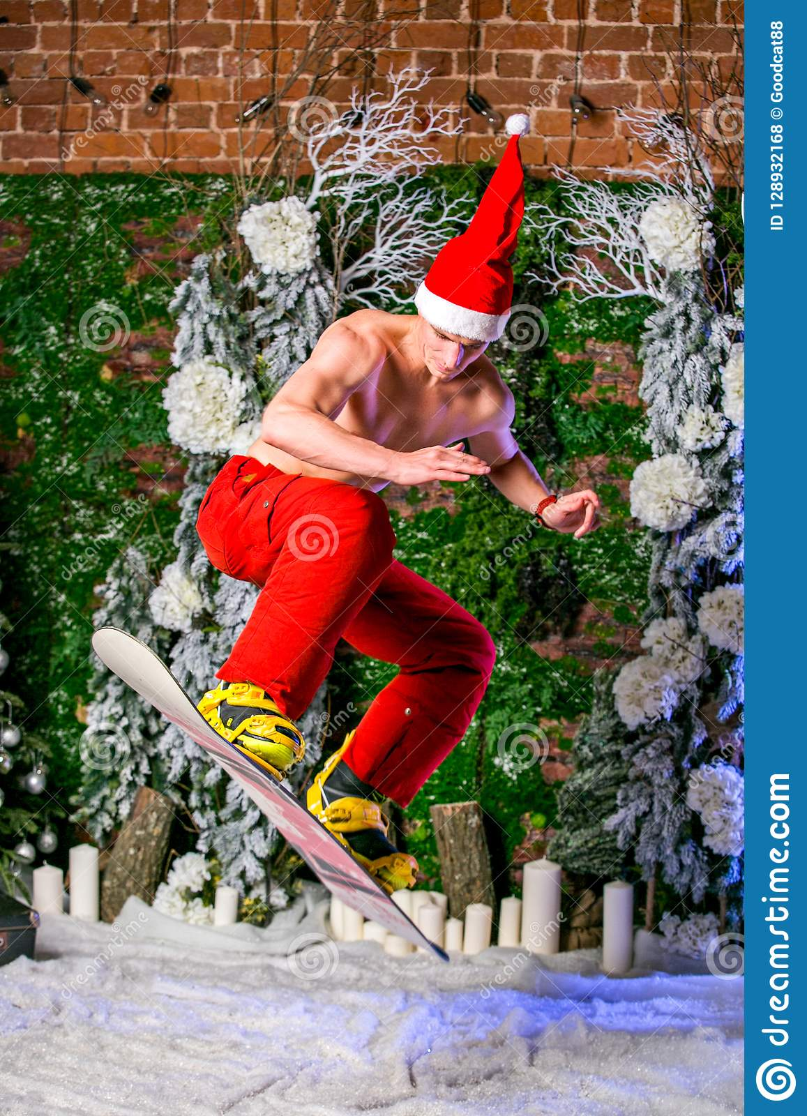 Young sporty young man in red pants and santa hat jumping with a snowboard