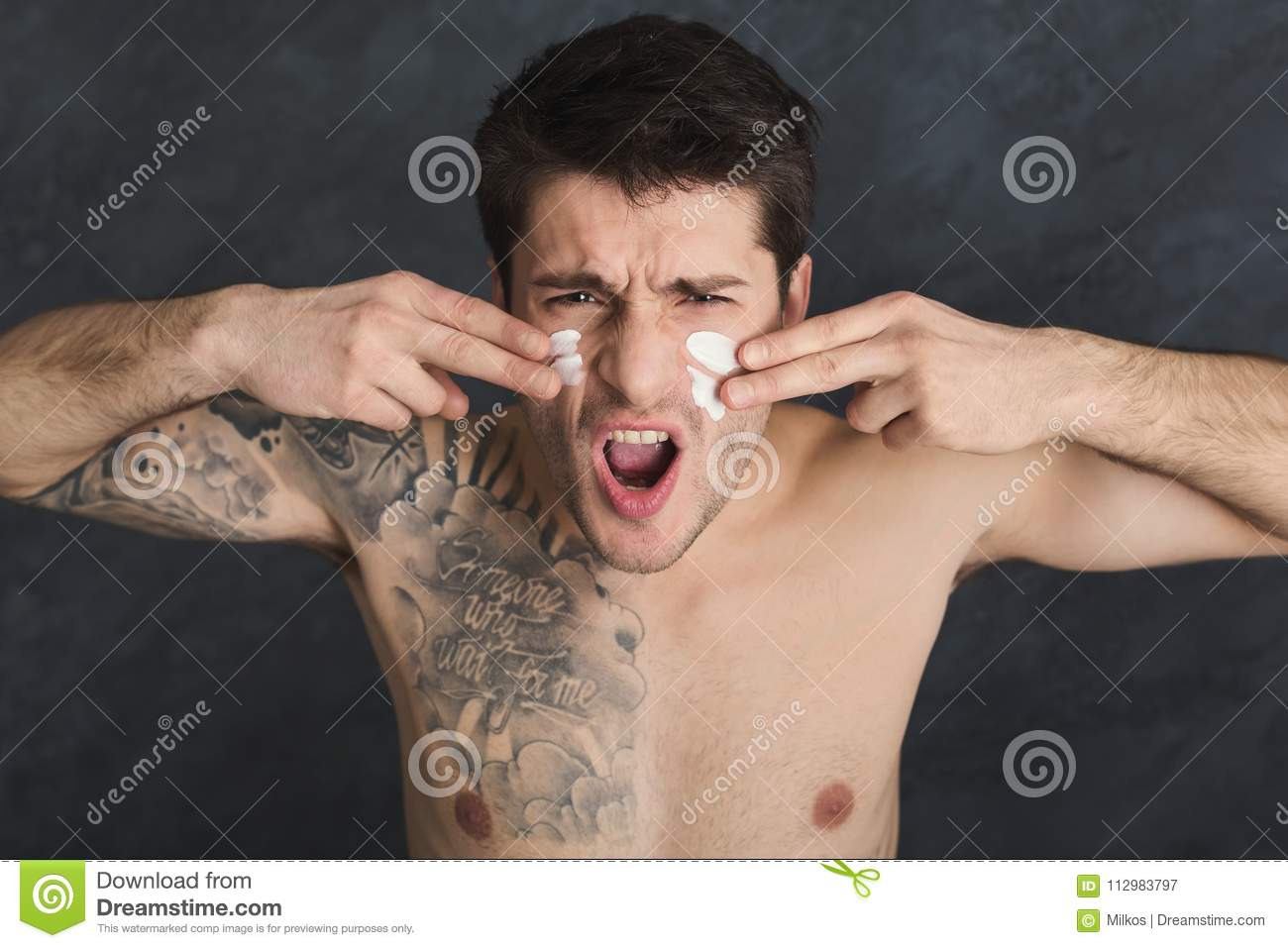 Young tattooed man put foam on face