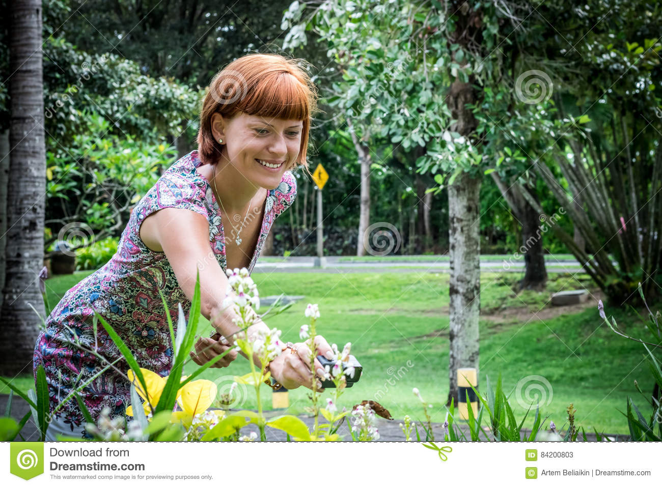 Young woman with action camera shooting butterfly in the plants. Nusa Dua park, tropical island Bali, Indonesia.