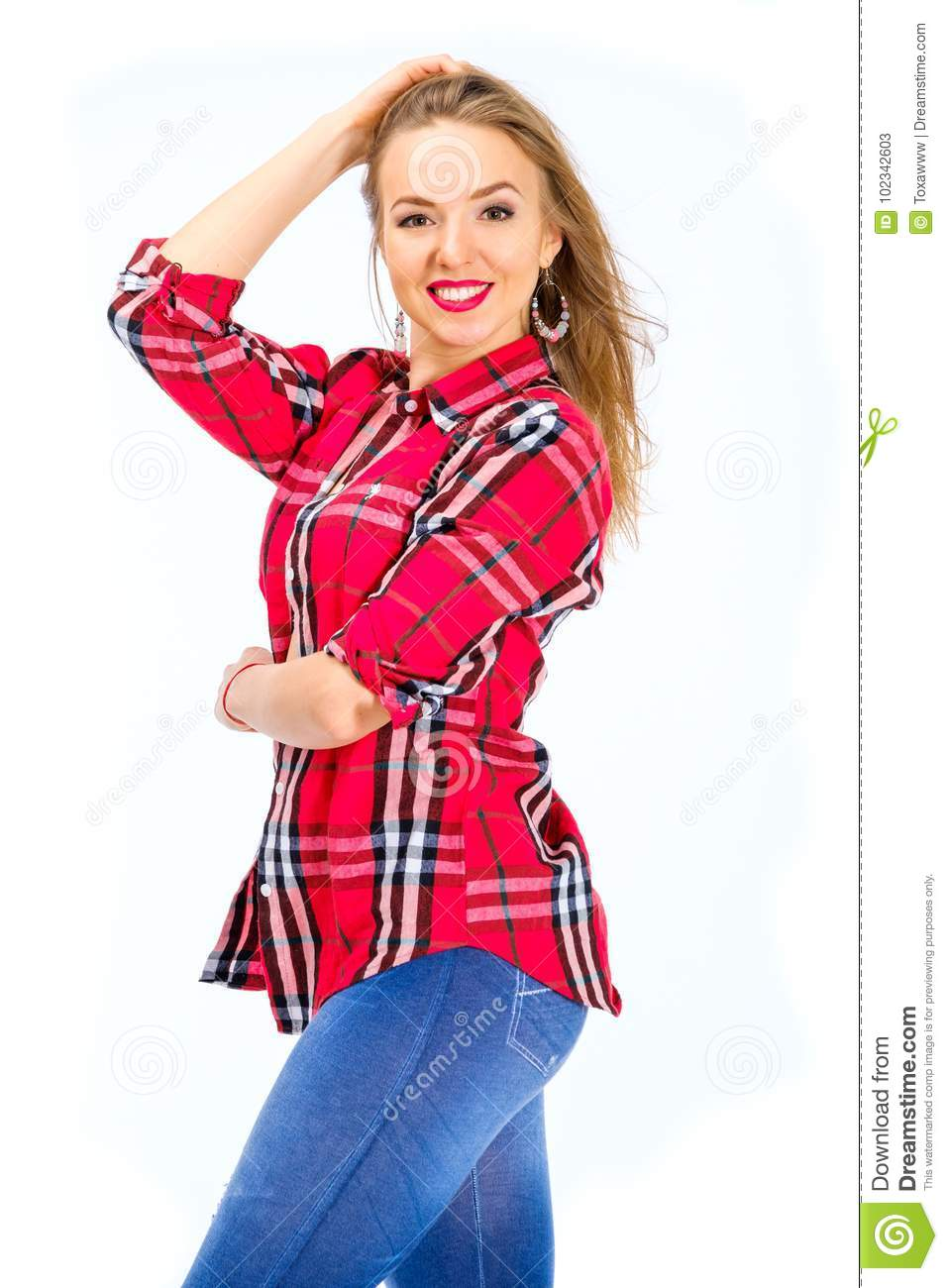 8509990a5a8 Young woman dressed in jeans and checkered shirt posing in studio isolated  on white. More similar stock images