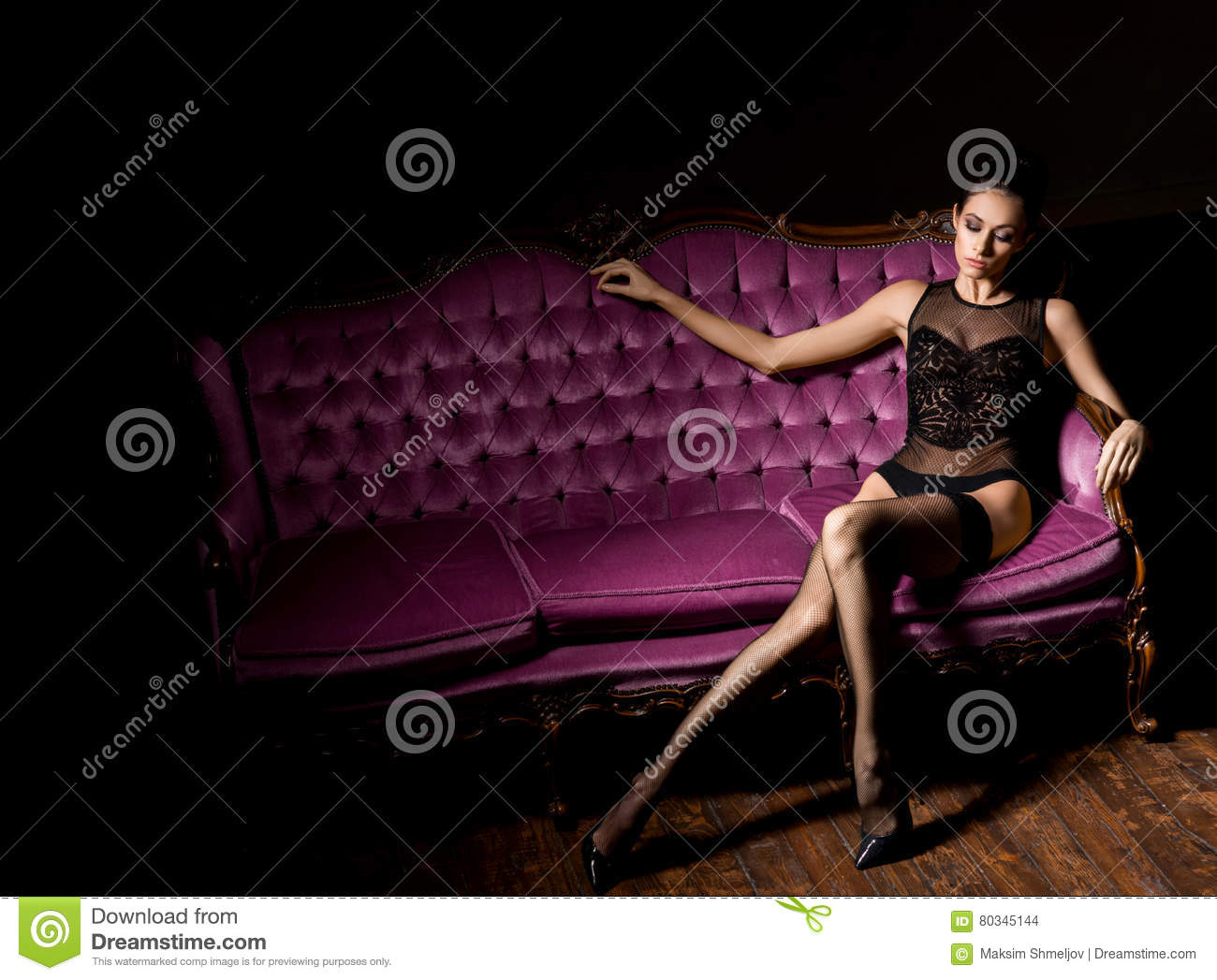 af034a933 and beautiful woman in erotic lingerie and stockings posing on a magenta  sofa in vintage interior.