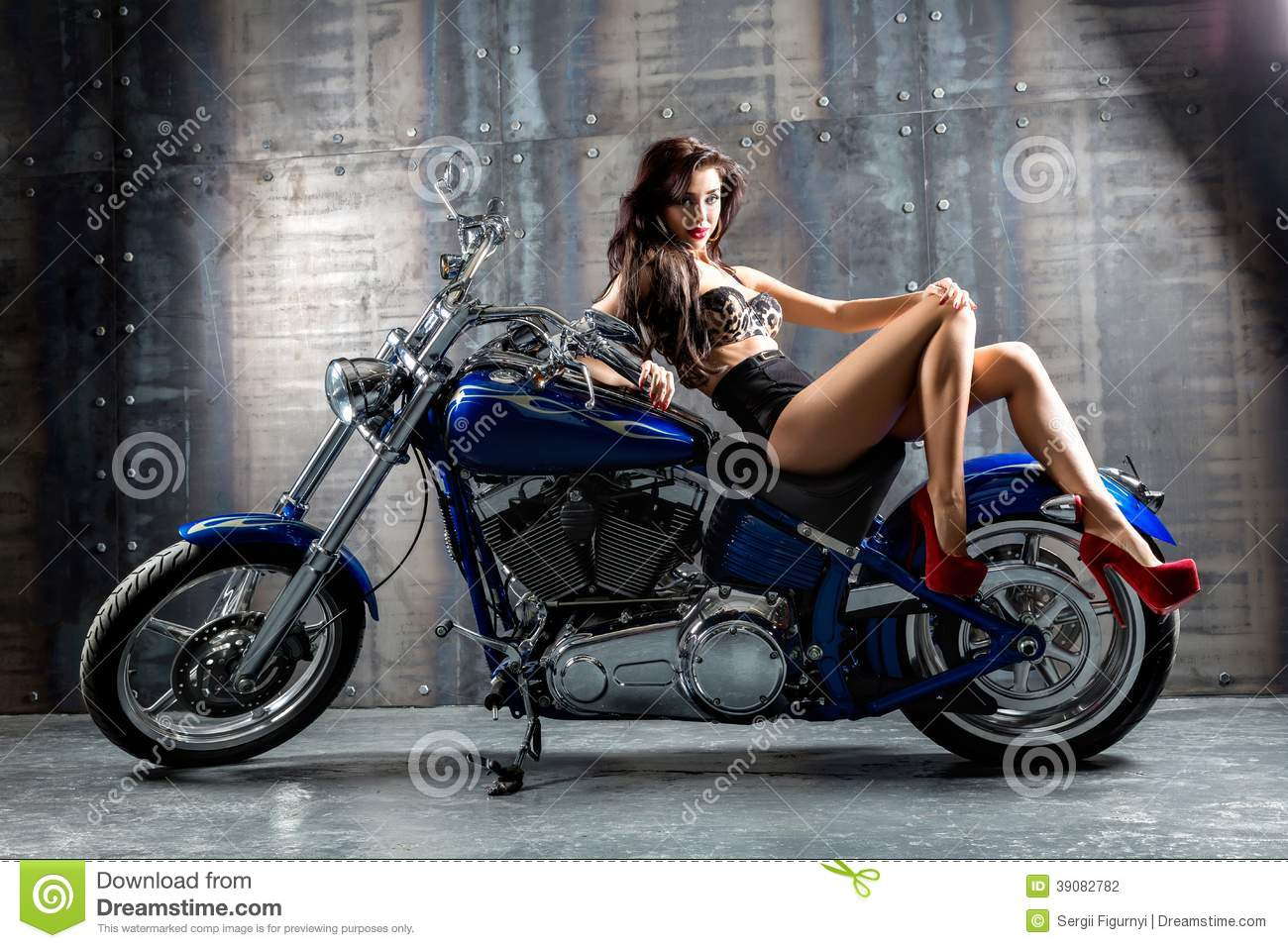 Young woman sitting on motorcycle.