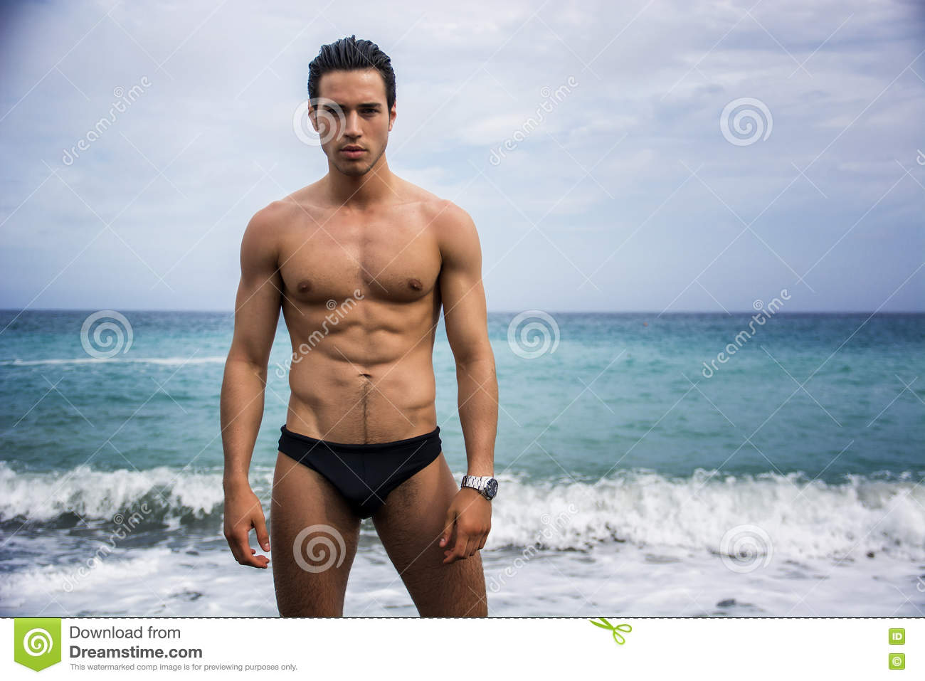 Young shirtless athletic man standing in water by ocean shore stock