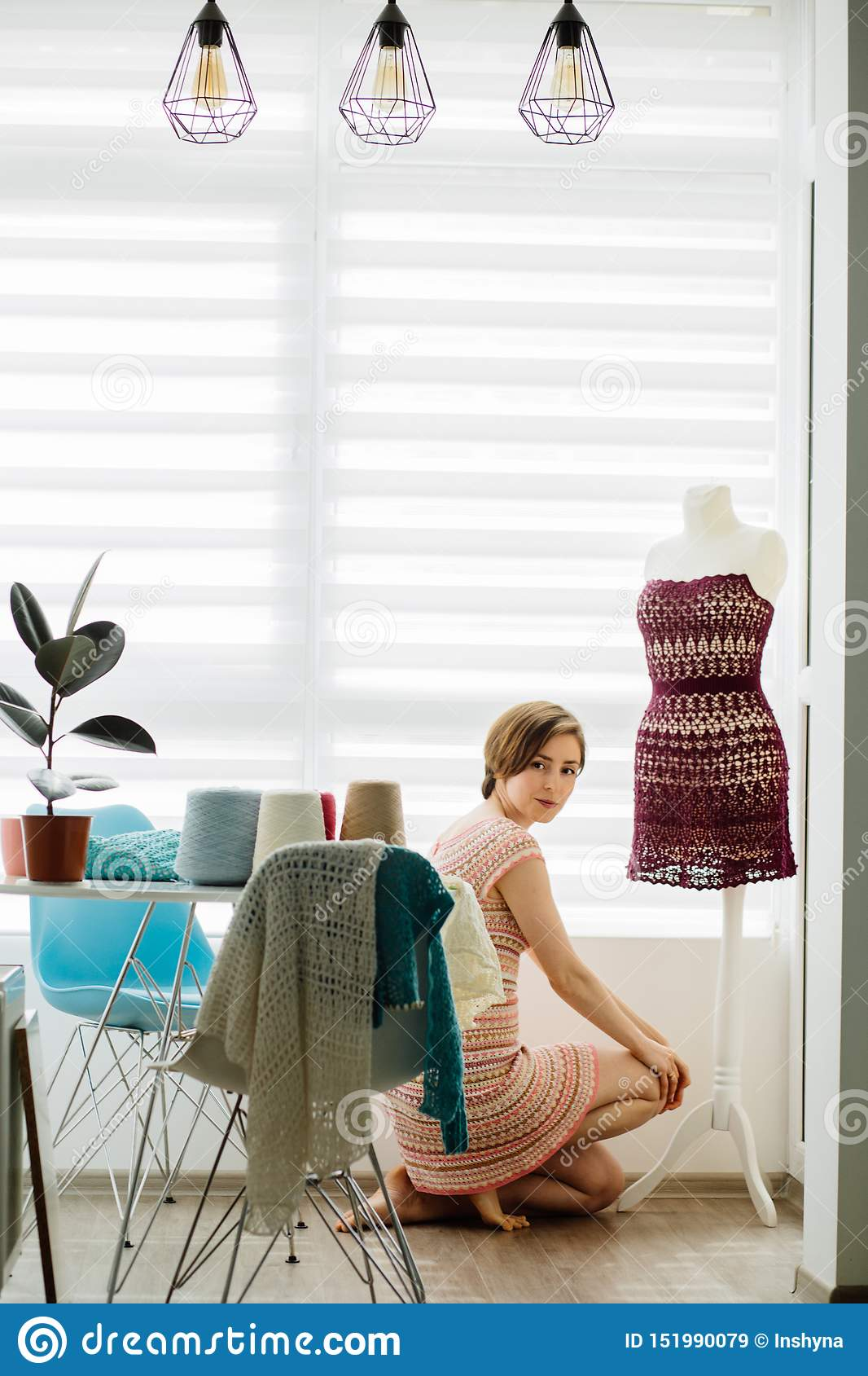 Young female clothing designer using dress dummy at cozy home interior, freelance lifestyle. Vertical shot