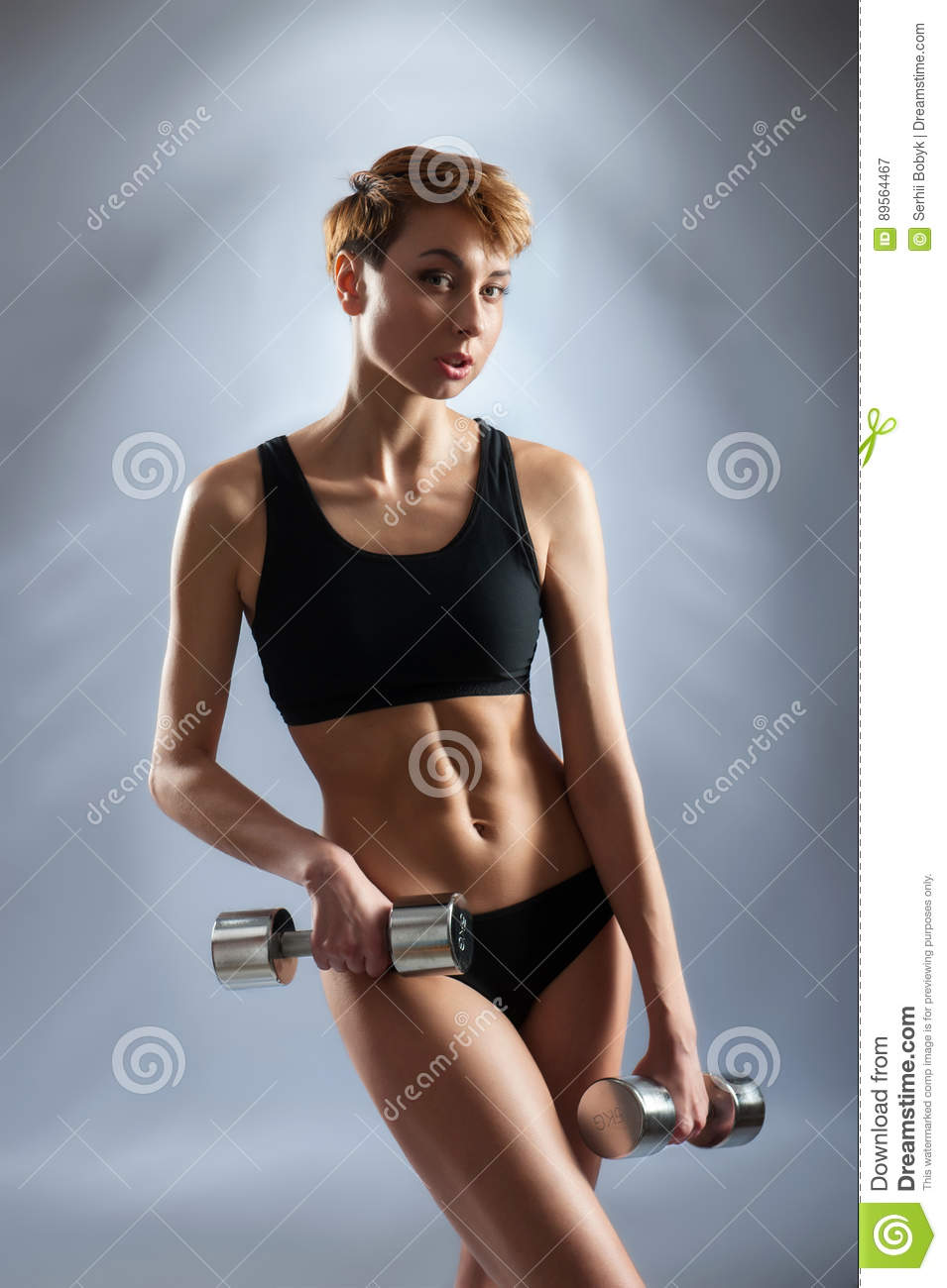 Young Short Haired Fitness Woman Posing With Dumbbells ...