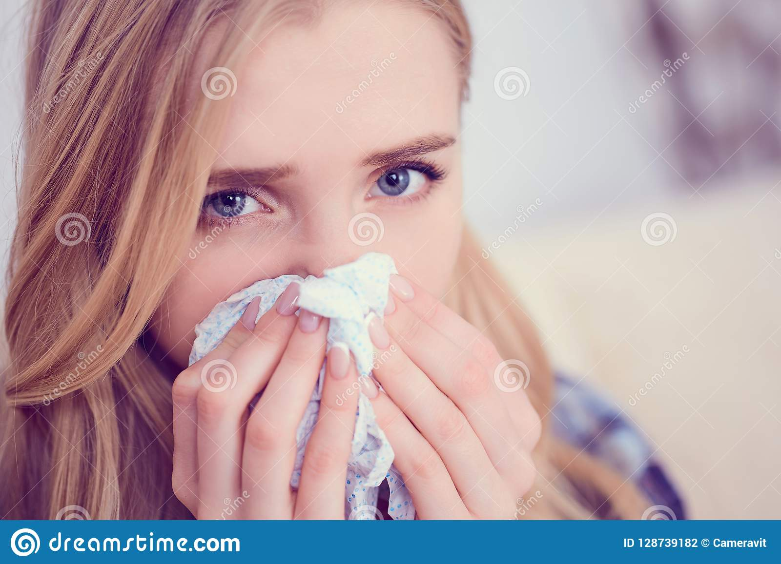 Young sick Caucasian woman sneeze at home on the sofa with a cold. Girl Used tissue paper blowing her nose. Medical and