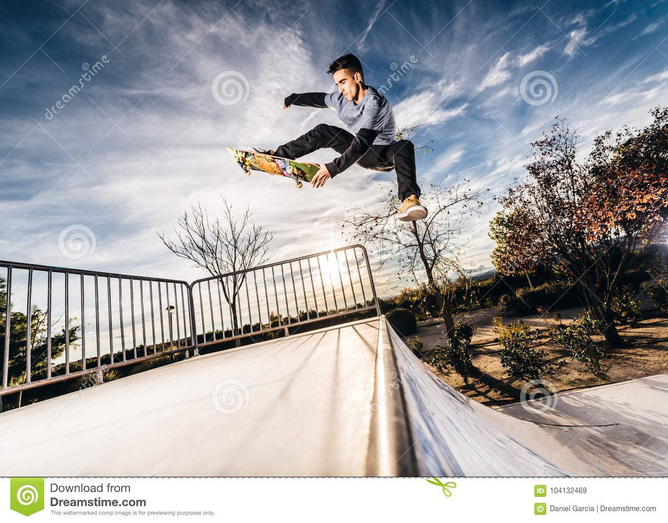 Young skater making a jump on Skatepark during sunset