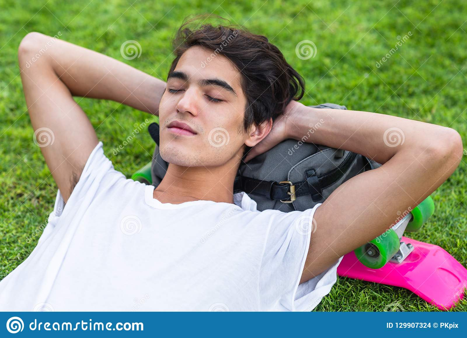 Young male skater resting on the grass with his eyes closed.