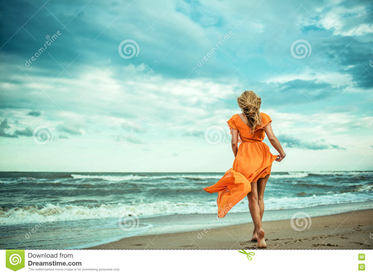 A young slender woman in orange dress is walking barefoot towards the storming sea