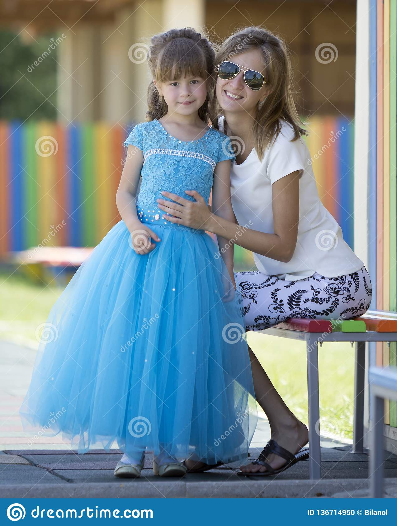 Young slim blond smiling mother, aunt or sister hugs small pretty preschool daughter girl in long nice blue evening dress on