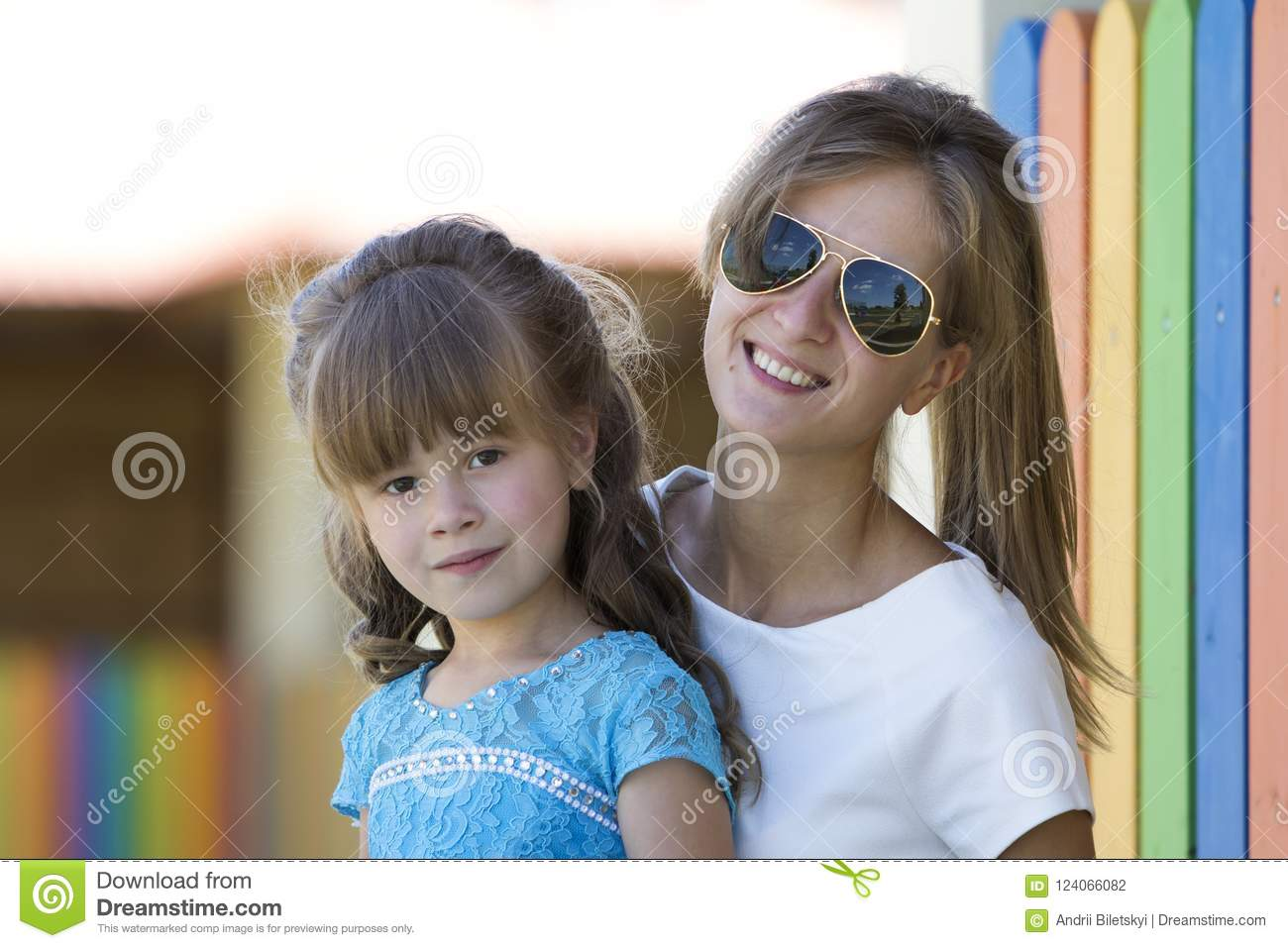 Young slim blond smiling mother, aunt or sister hugs small pretty preschool daughter girl in nice blue dress on blurred colorful p