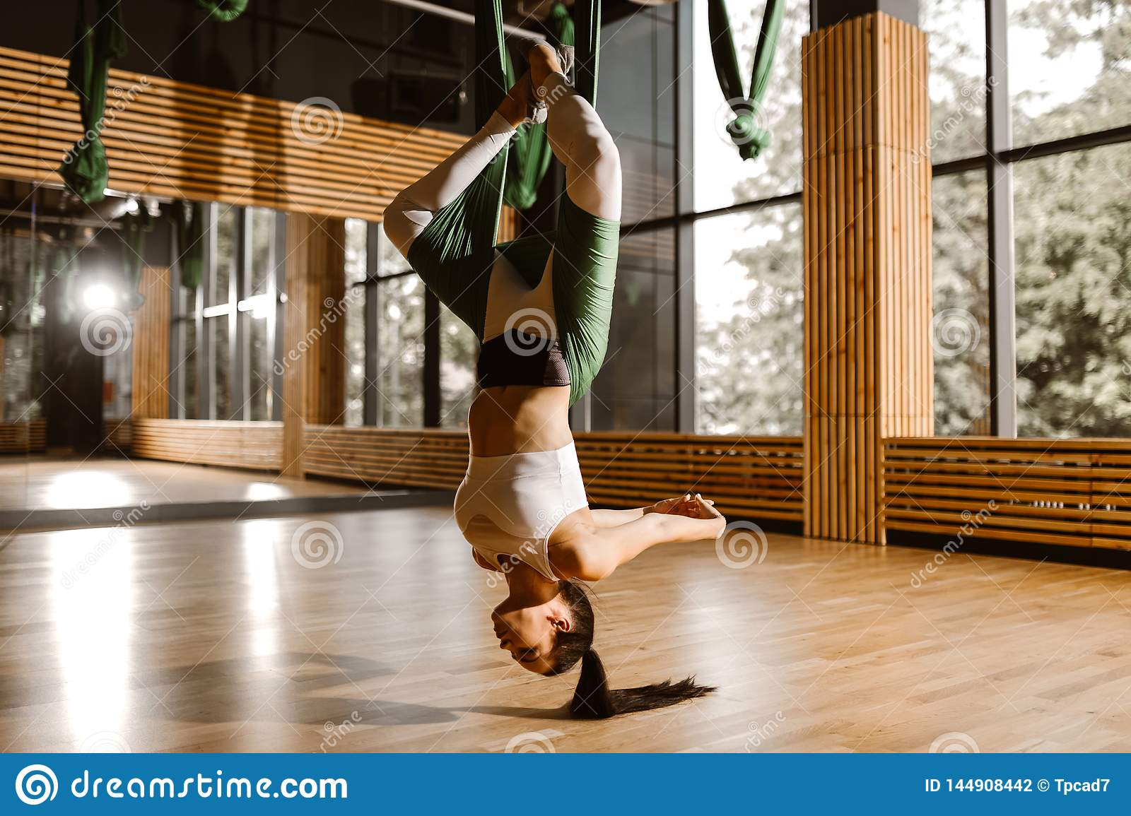 Young slim dark-haired girl dressed in white sports top and tights is doing yoga on green hammock