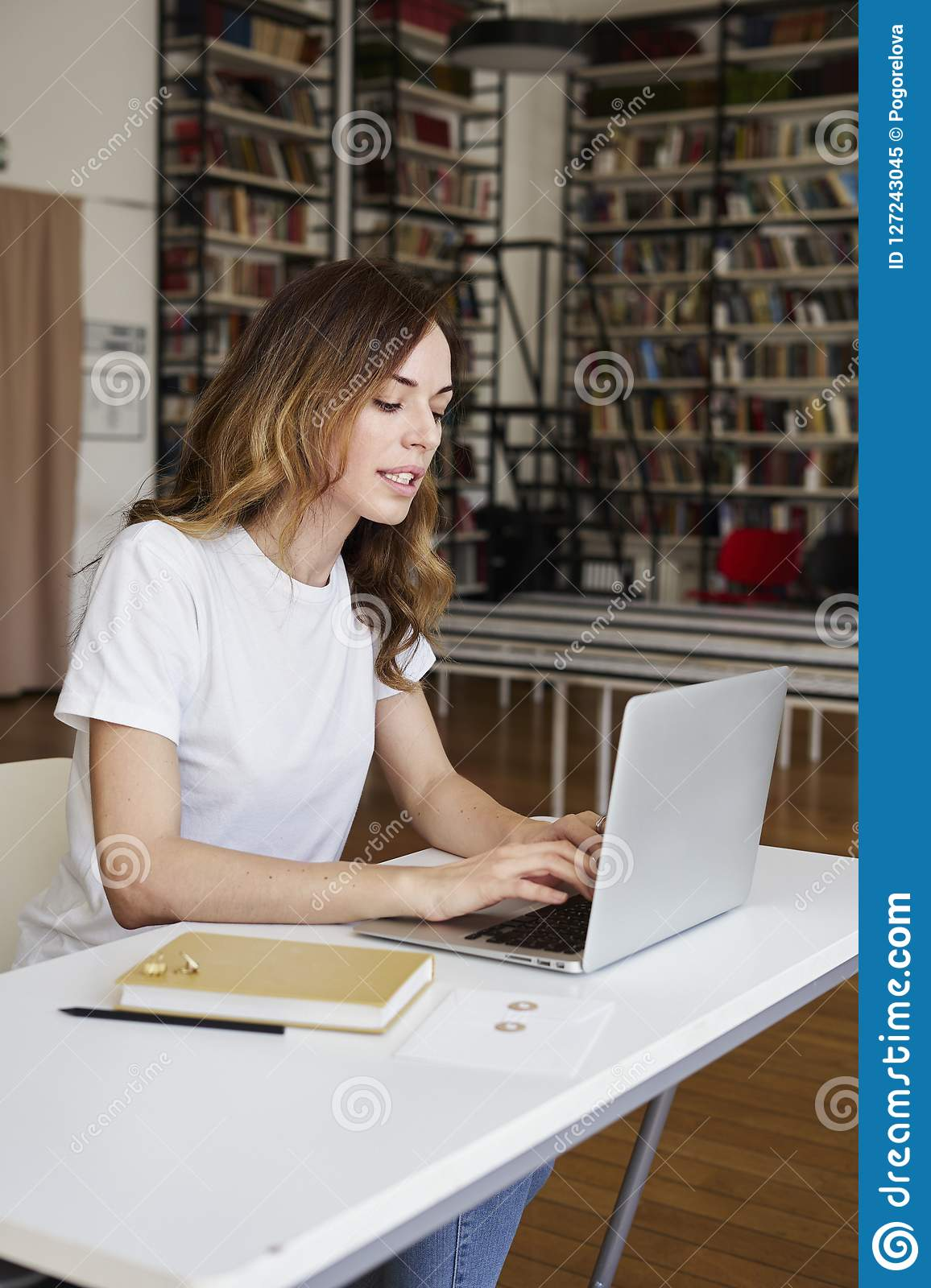 Young smart woman long hair analyst working at co-working office on laptop, bookshelf in library