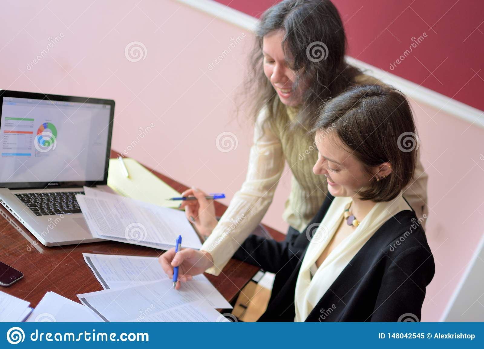 Young smartly dressed lady helps another young lady to work with documents, fill forms and sign. They sit together in a vintage