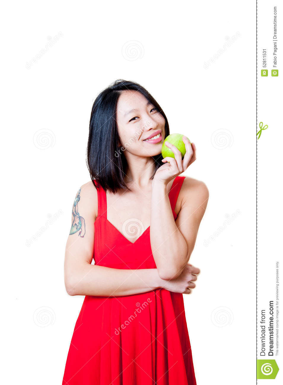 Young smiling asian woman red dress with green apple isolated stock