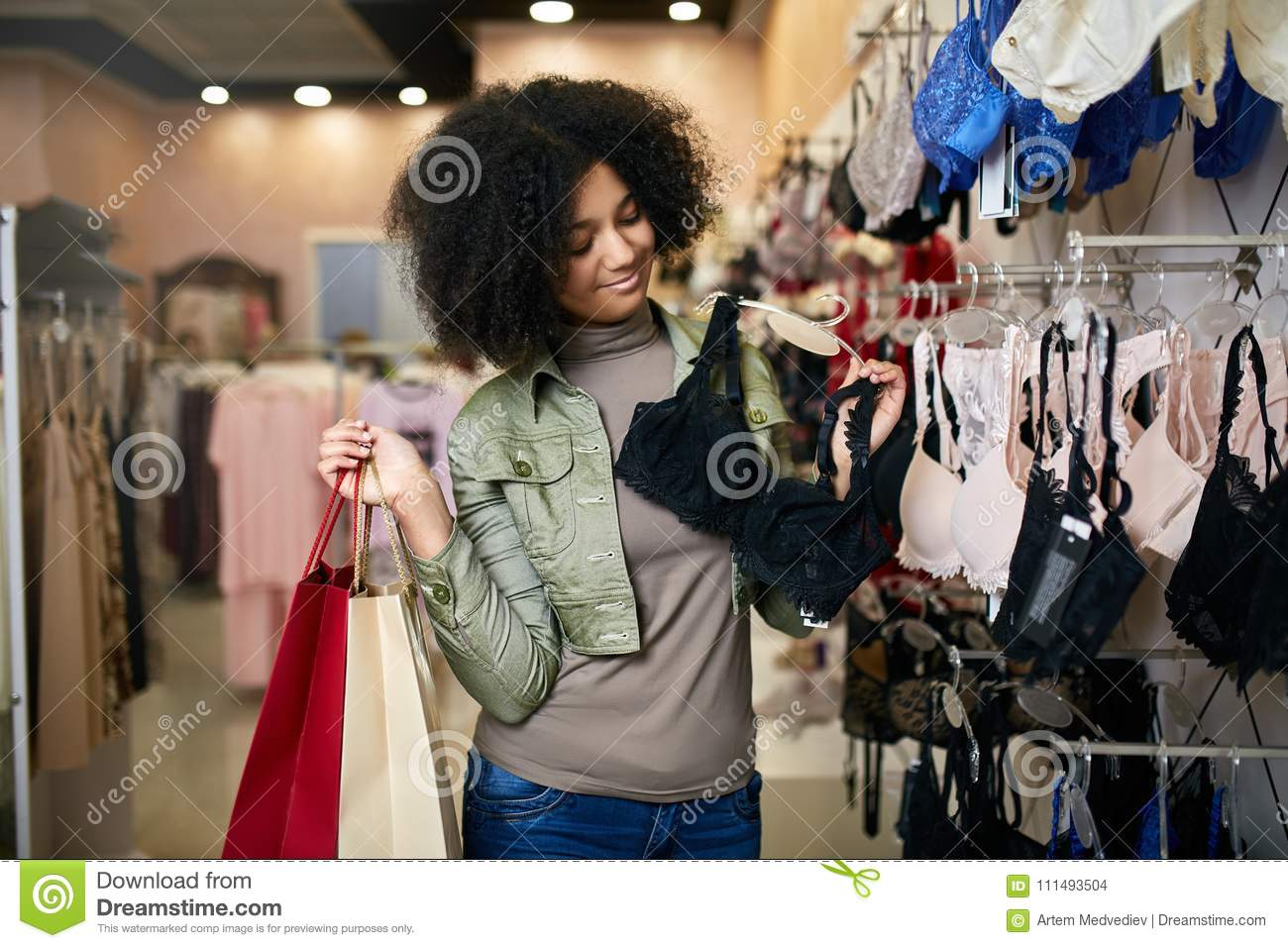 Young smiling attractive african american woman choosing right bra size in lingerie store boutique. Black mixed race