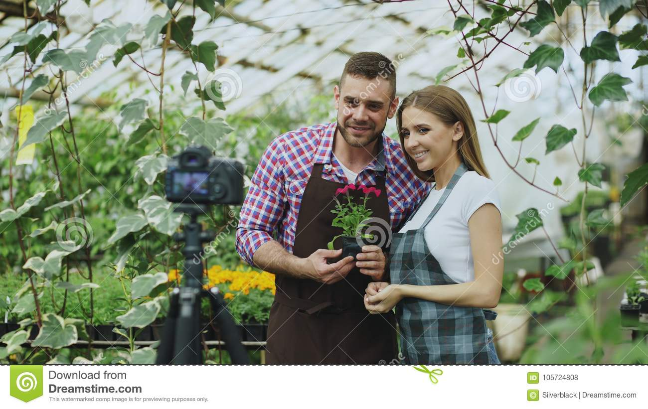 Young smiling blogger couple gardeners in apron holding flower talking and recording video blog for online vlog about
