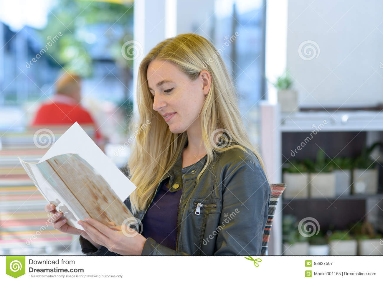 Young blond woman reading menu