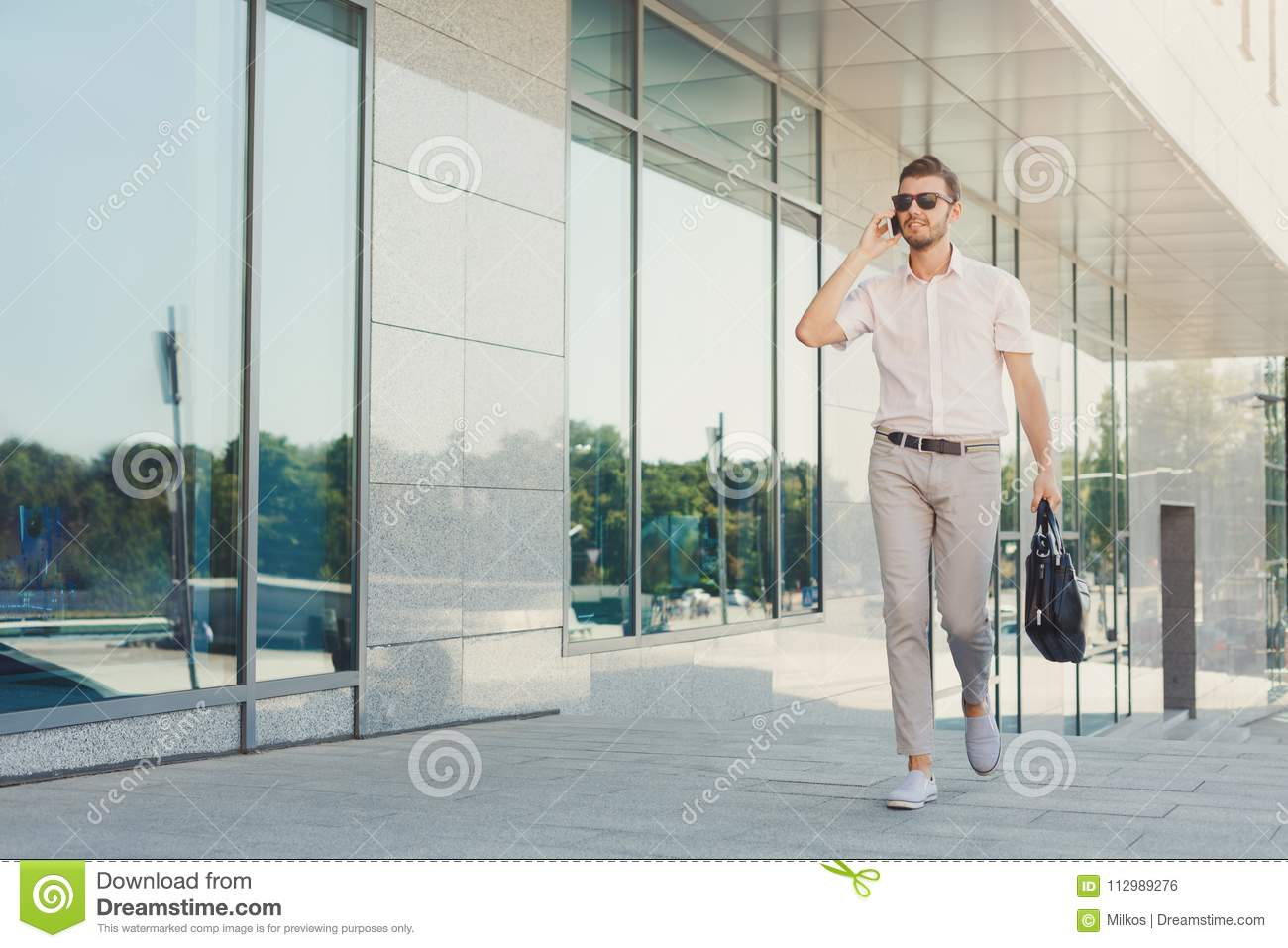 Confident happy businessman making a phone call outdoors