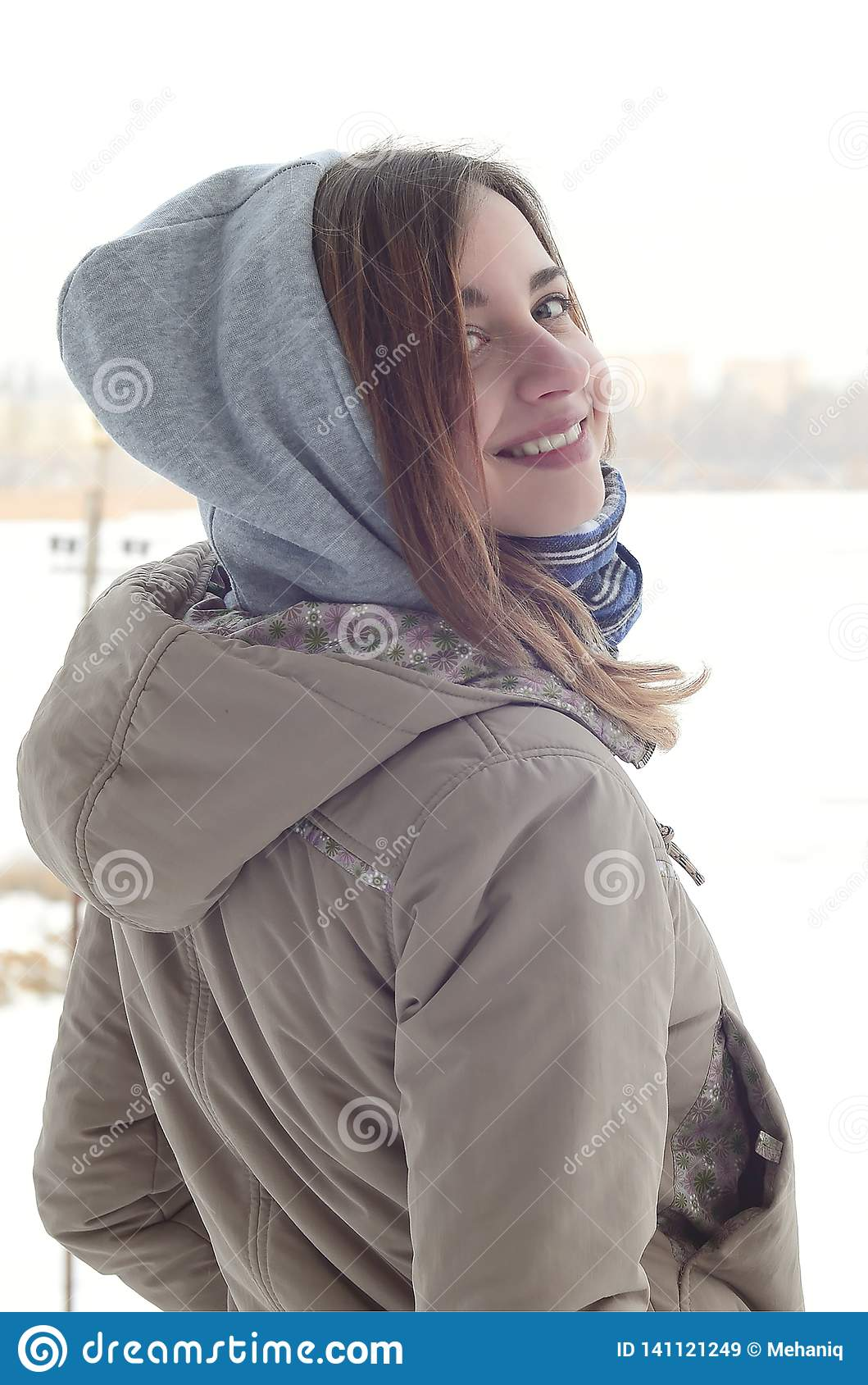A young and smiling Caucasian girl looks around the horizon line between the sky and the frozen lake in winter time