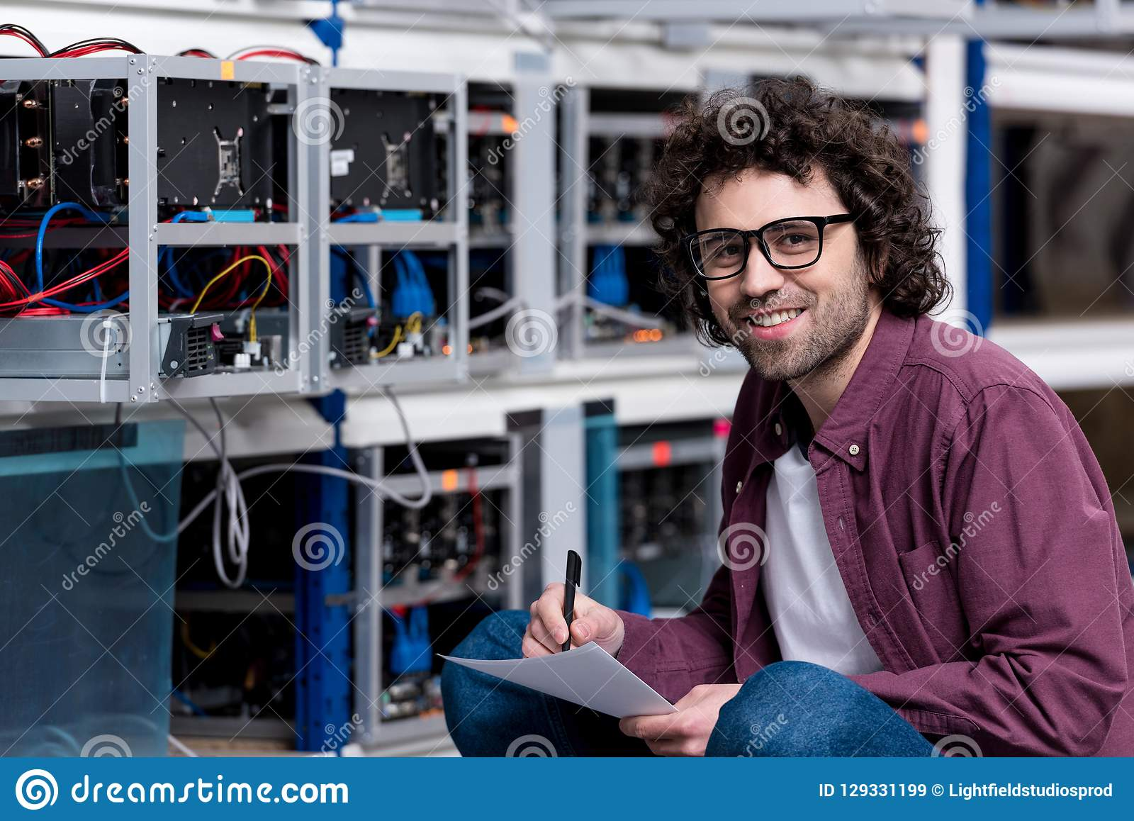 Young smiling computer engineer sitting on floor and writing at cryptocurrency mining farm royalty free stock images