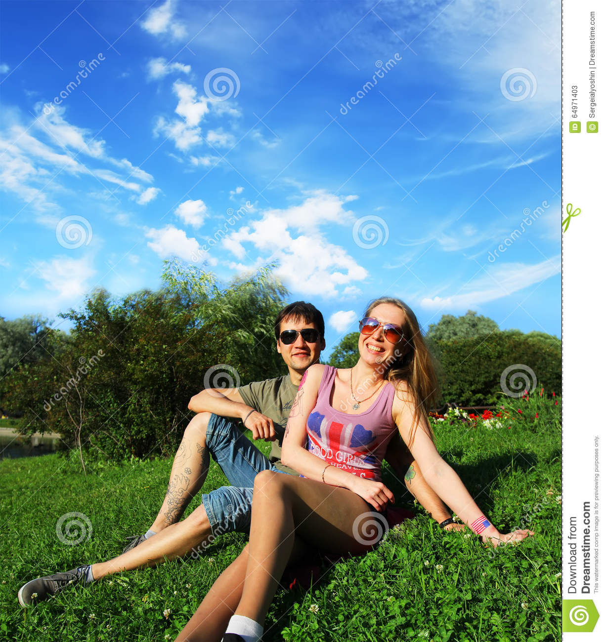 Young Smiling Couple In Sunglasses Sitting In A Park In