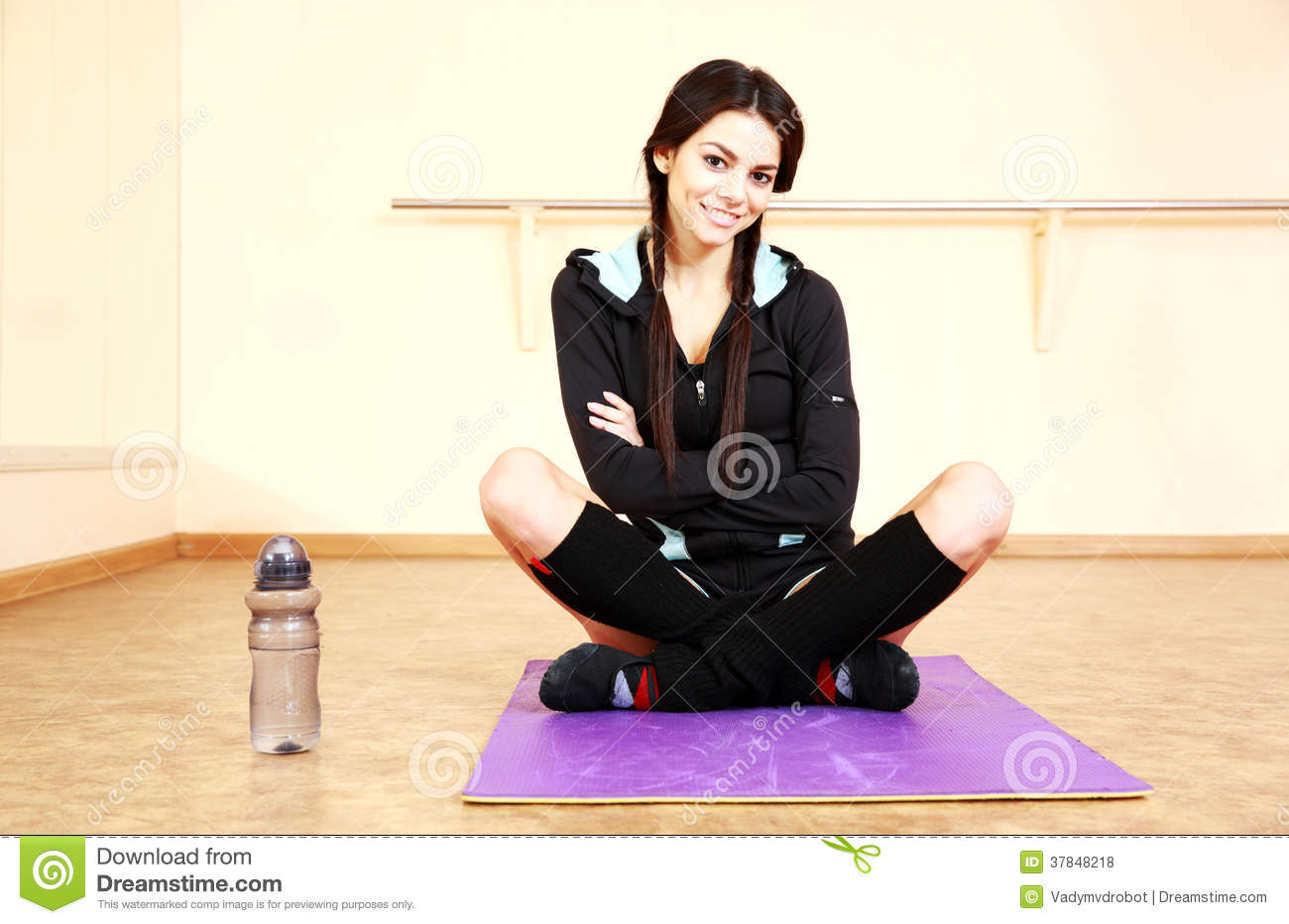 Young smiling fit woman sitting on the yoga mat