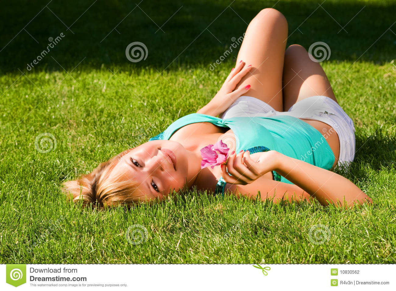 Young Smiling Girl Lies On Grass On The Back Stock