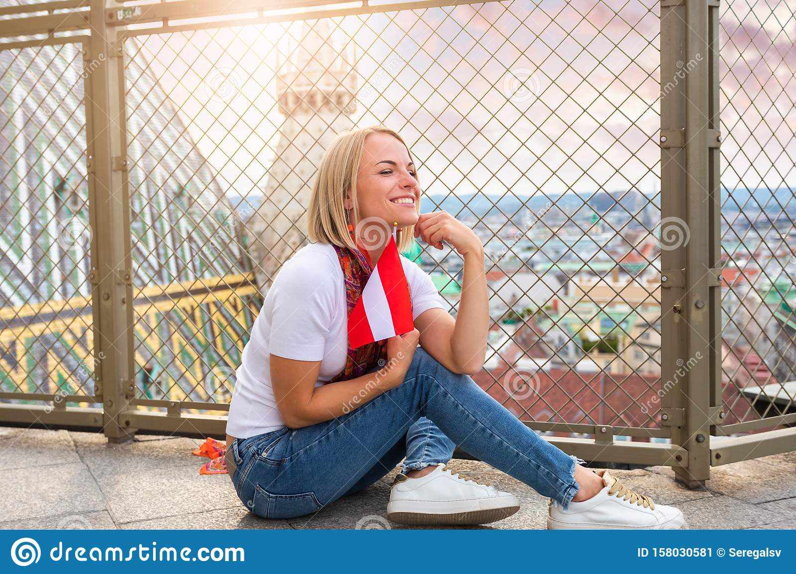 A young girl sits on the floor against the background of the panorama of Vienna and against the roof of St. Stephen`s