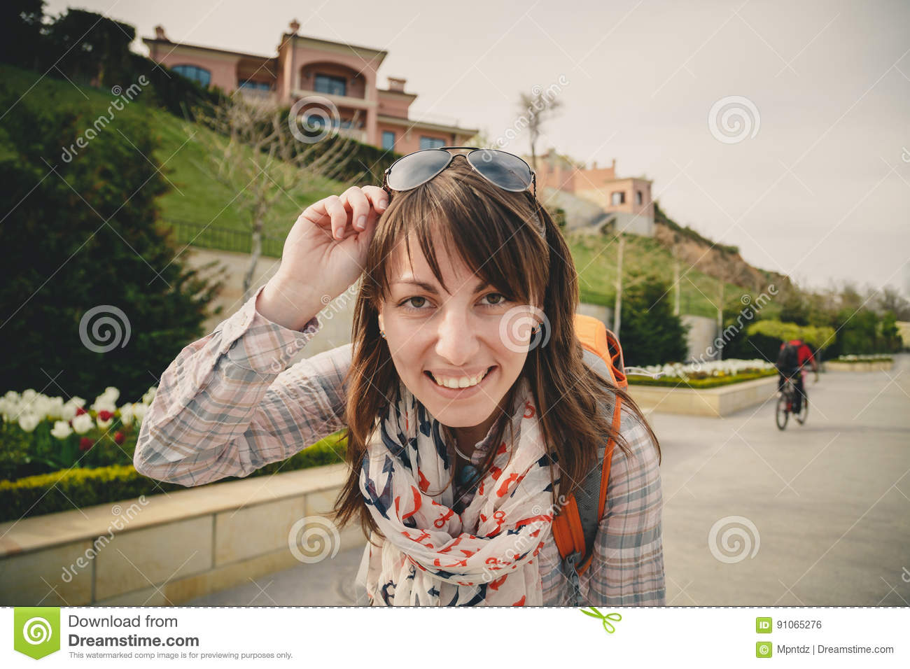 ac391b93bf3 Young smiling happy girl in pink shirt and anchors scarf with sunglasses on  head and orange backpack looking at camera outdoors. Healthy lifestyle  concept