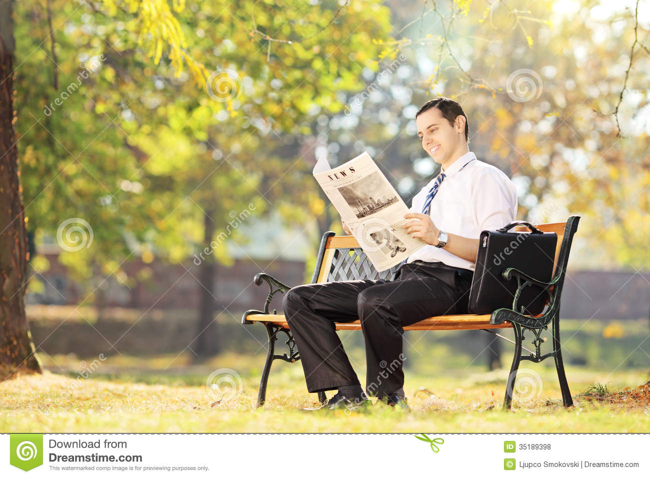 young smiling man seated on bench reading newspaper in a park stock