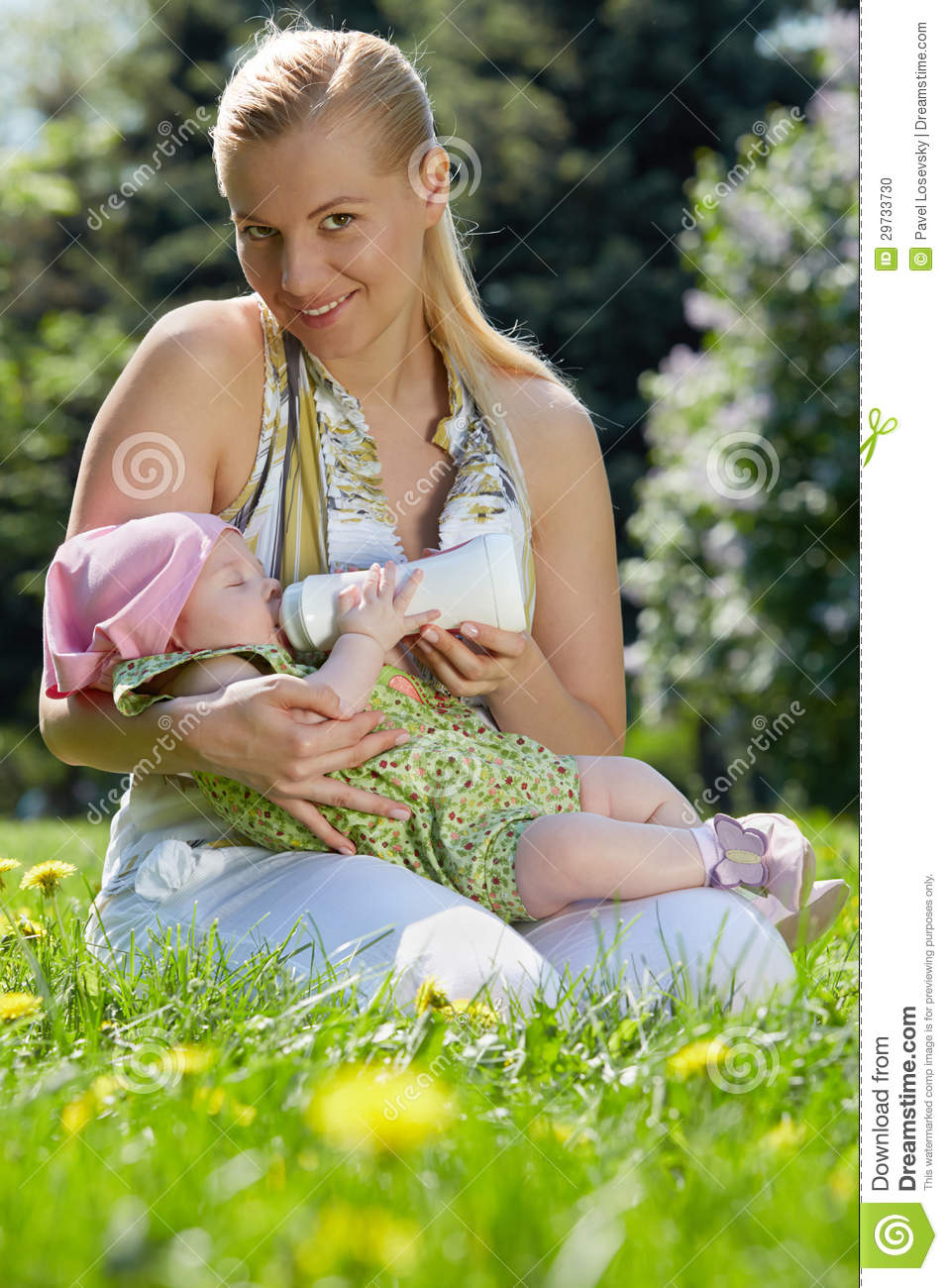Young smiling mother feeds her baby with milk