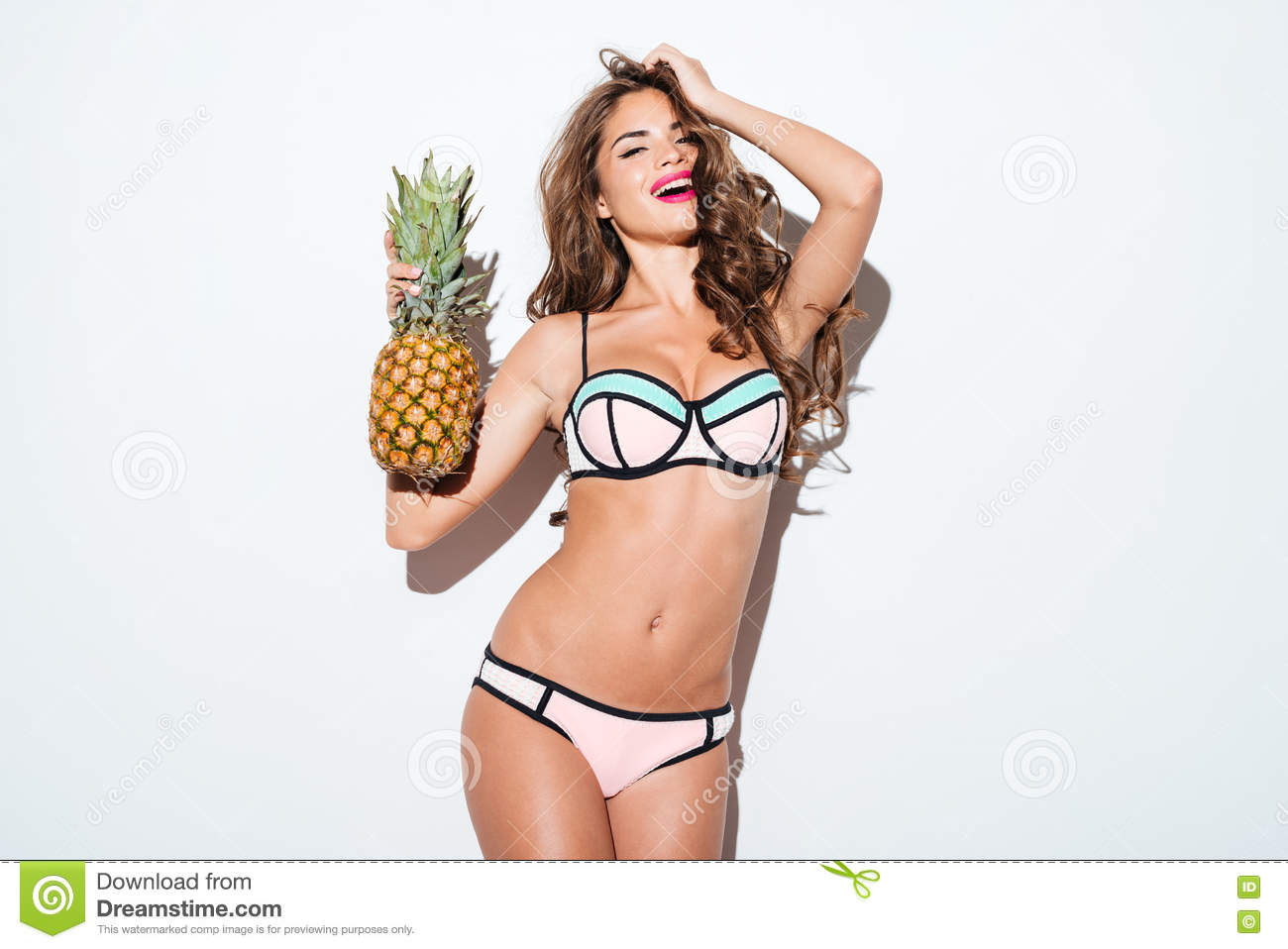 Young smiling pretty girl holding pineapple and posing