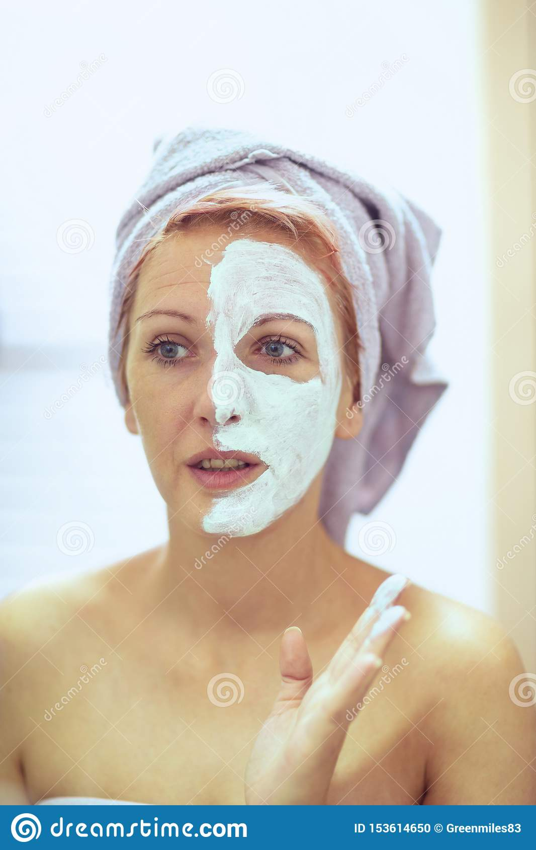 Smiling Woman applying facial mask. Beauty treatments