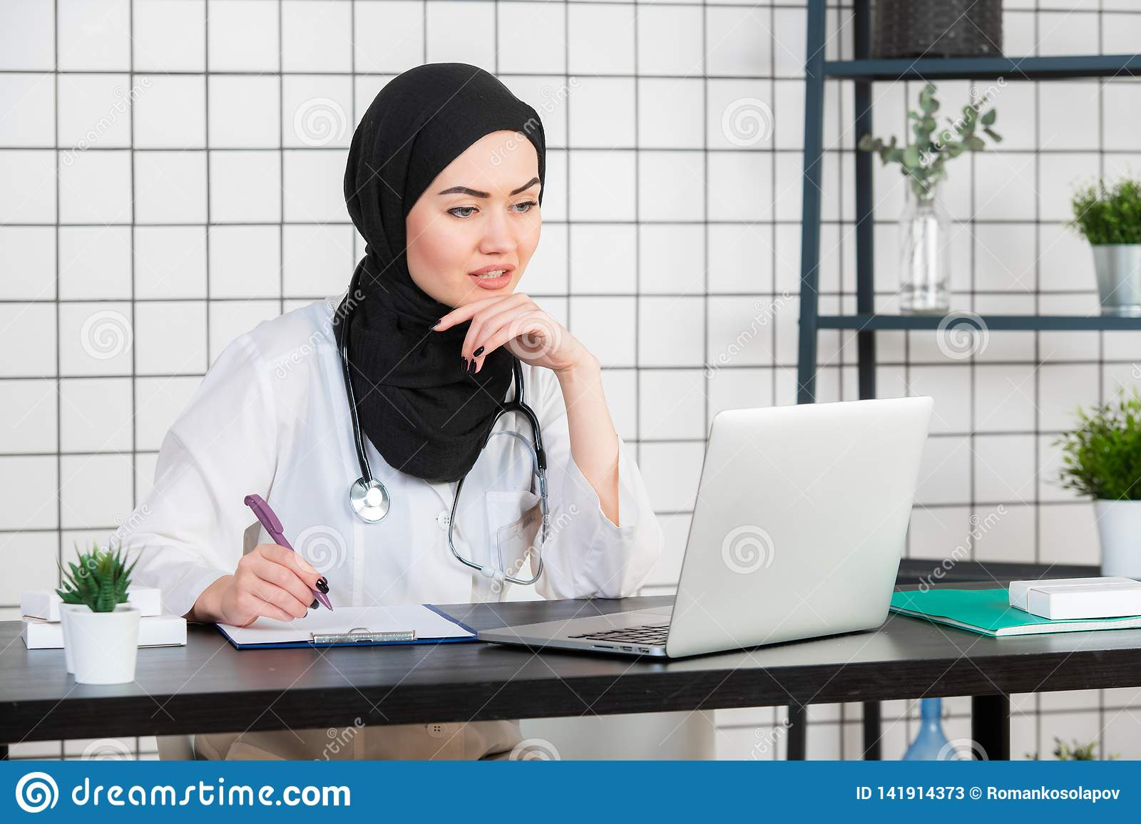 Young smiling woman sitting at desk, working on computer with medical documents in light office in hospital. Female