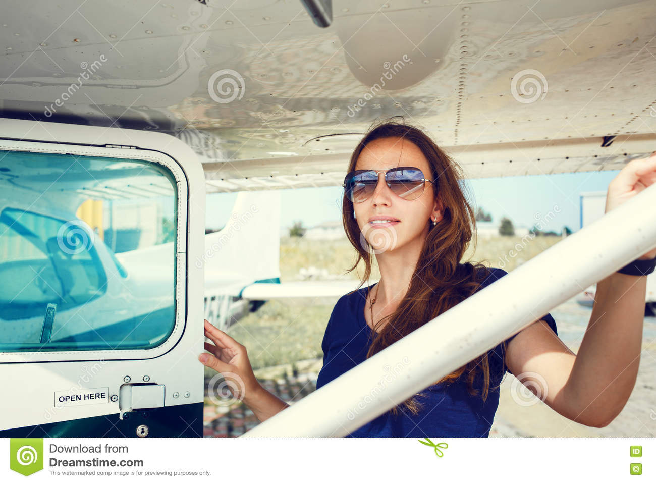 Young Smiling Woman Standing Near Private Plane Stock Photo