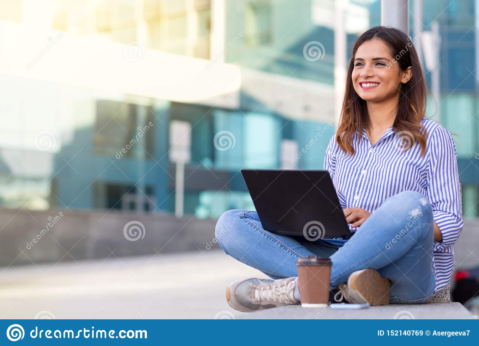 Young smiling woman using computer and drinking coffee outdoors with copy space