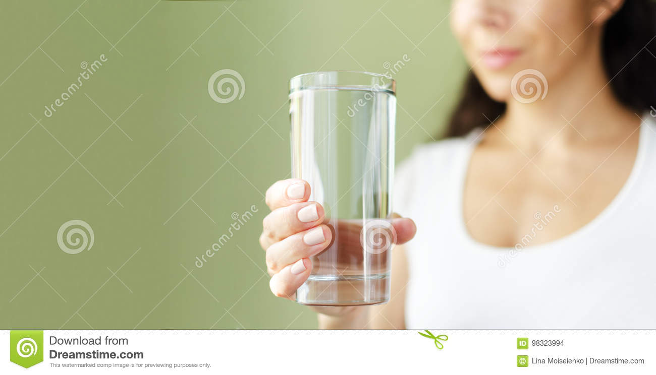 Young smiling woman in white t-shirt holds out glass of water. Green background. Copy Space