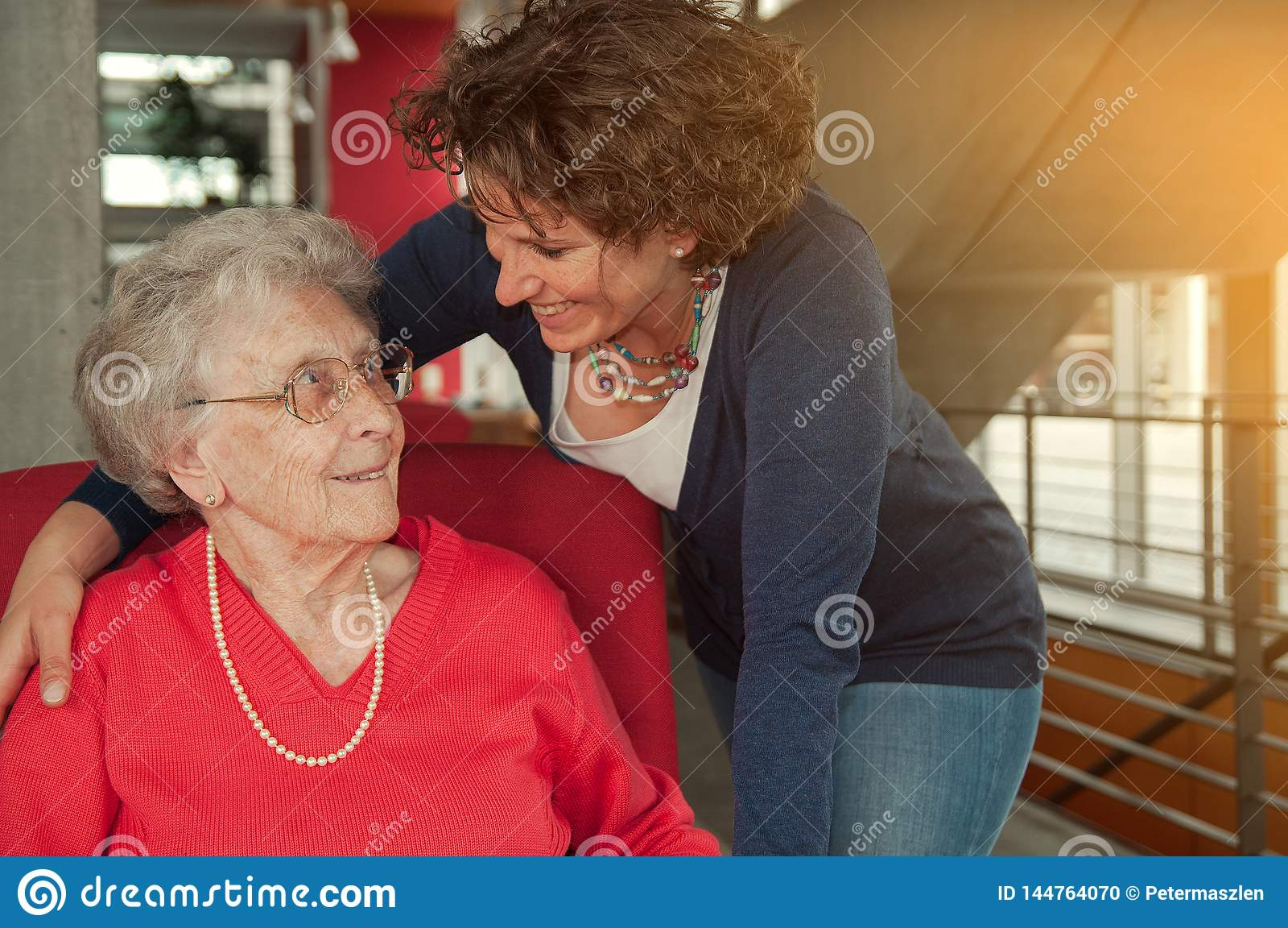 Young smiling woman embracing senior woman