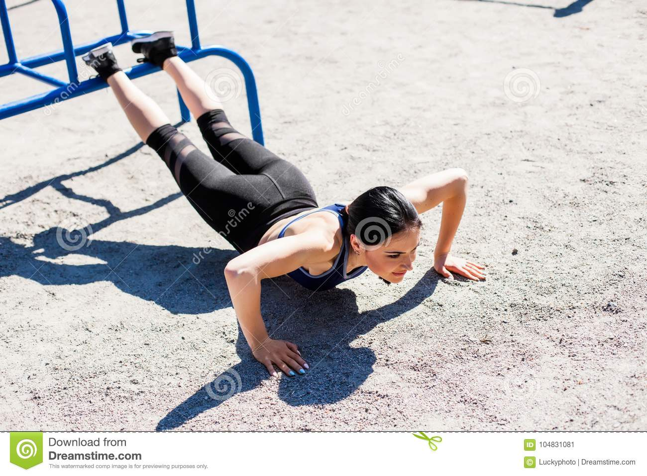 94e5bbed1a20b Sportive teen in a bright blue sport bra and black leggings doing push ups  on the sport playground. Photo of an athlete girl with a beautiful sports  body