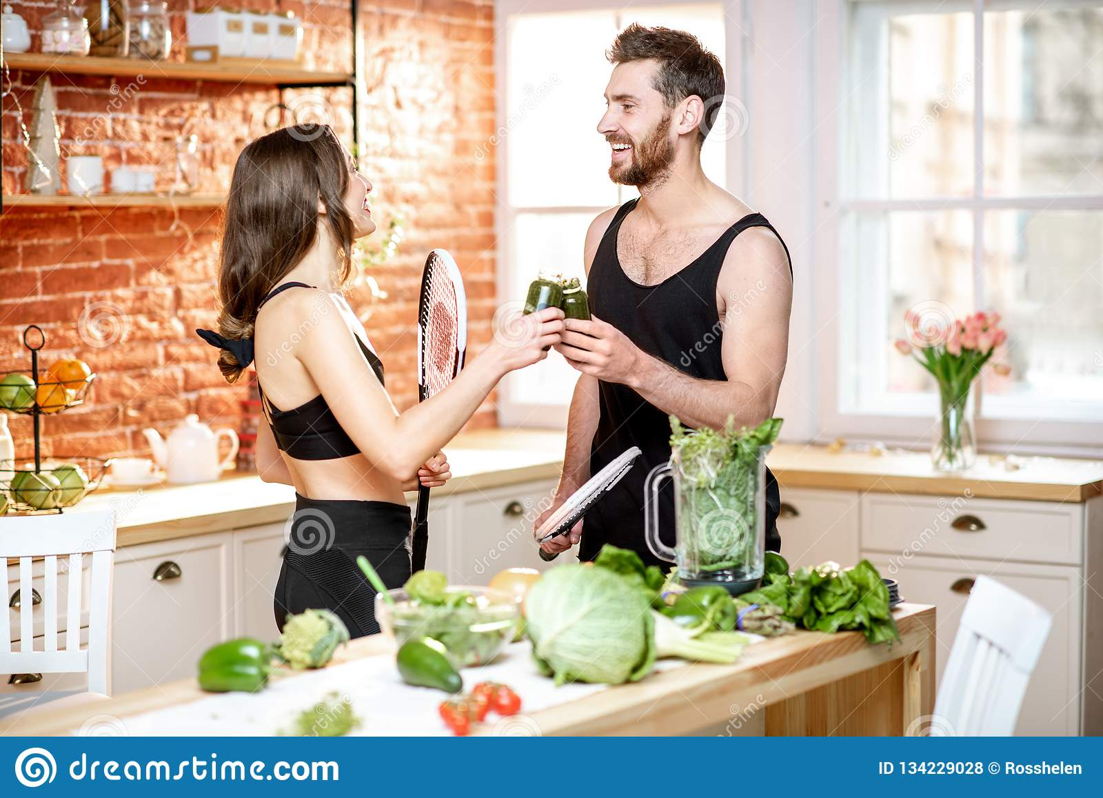 Sports couple eating healthy food on the kitchen at home