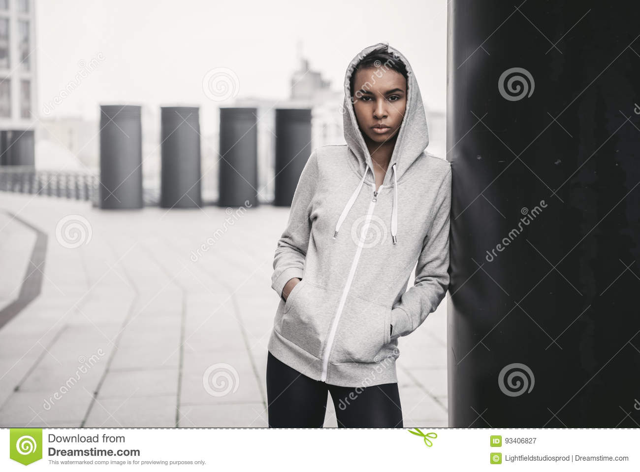 Young sportswoman in hood posing with hands in pockets and looking at camera