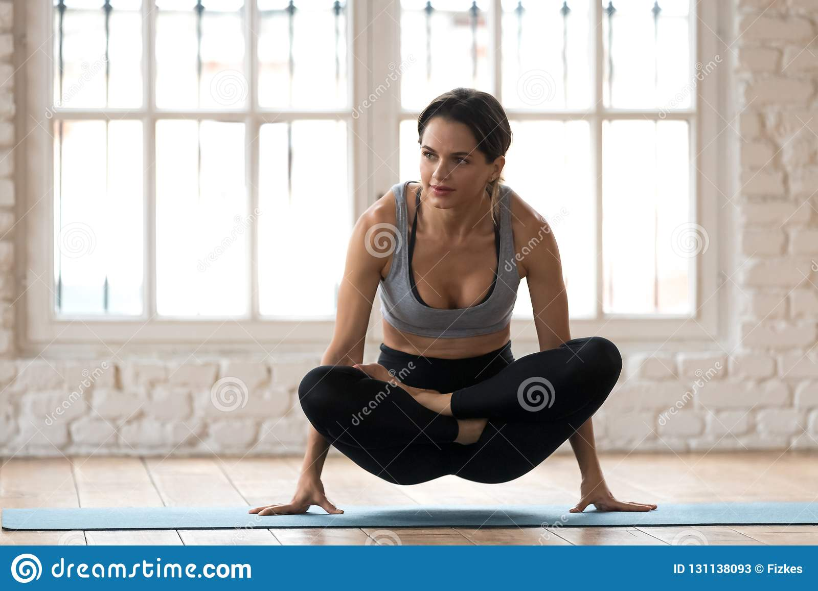 ce2666a57b Young sporty attractive woman practicing yoga, doing Scale exercise,  Tolasana pose, working out, wearing sportswear, black pants and top, indoor  full length ...