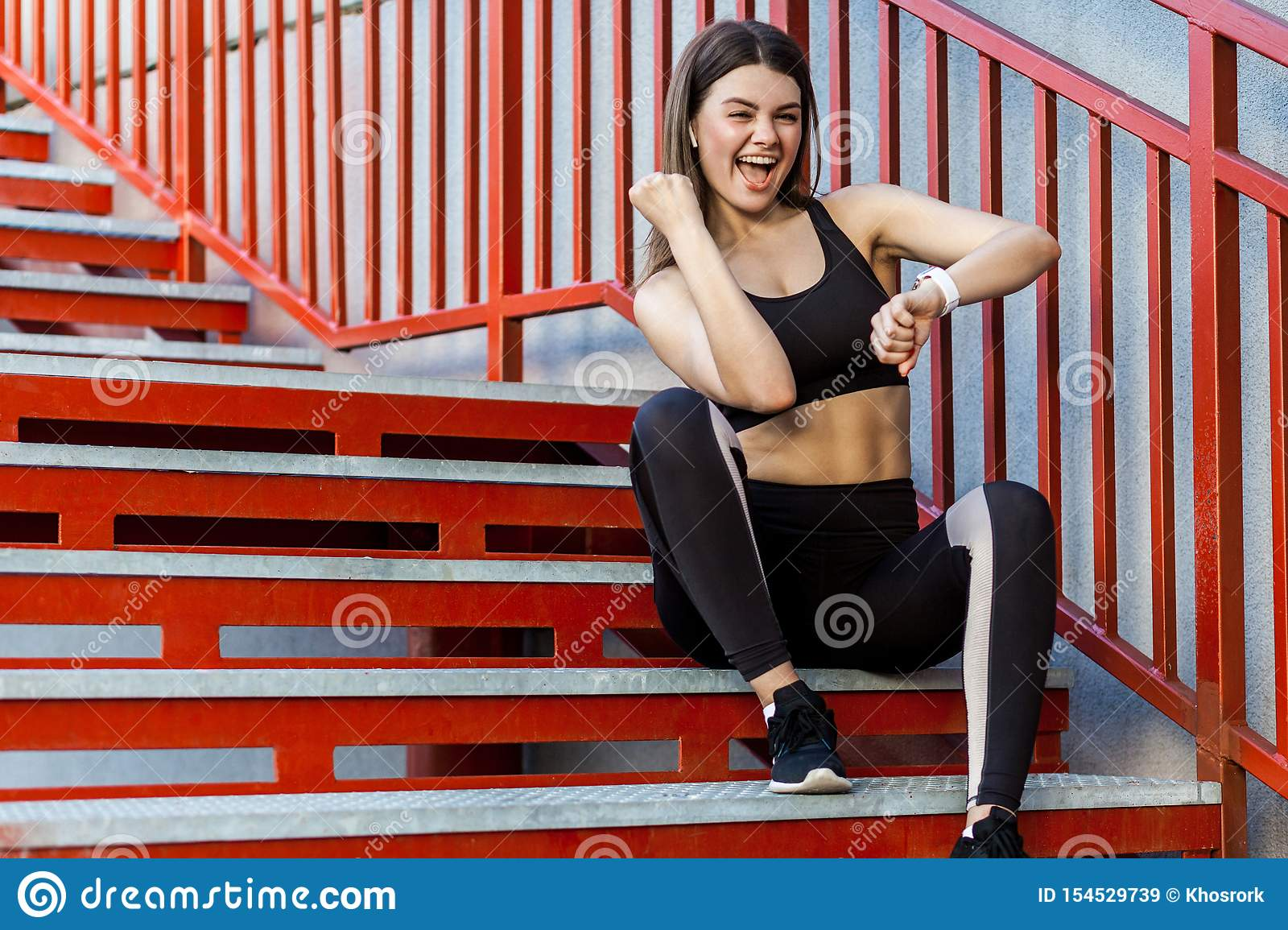 Young sporty beautiful woman having a break sitting on the red stairs after morning jogging, checking on smartwatch and celebrate