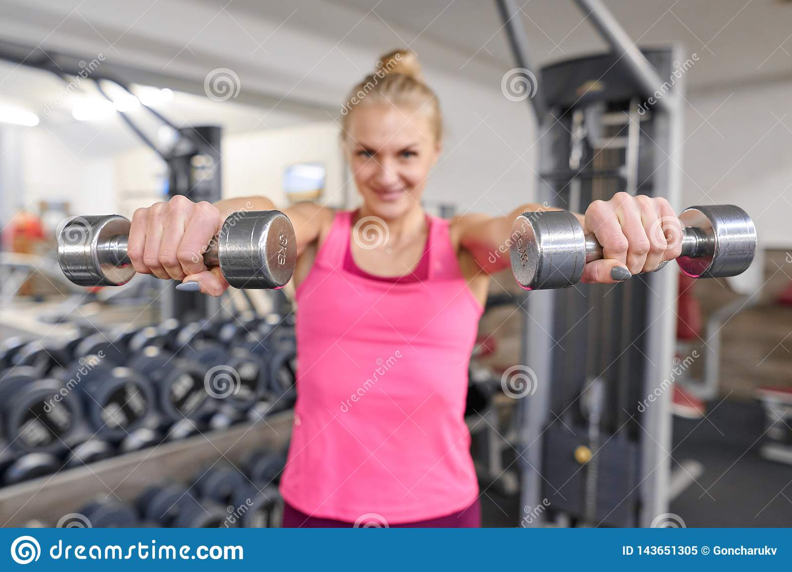 Young sporty blond woman in the gym. Woman holding metal weights, focus on kettlebells. People fitness sport healthy lifestyle