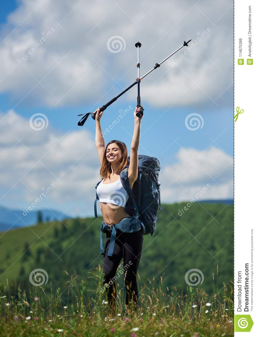 2048359314c Sporty Woman Tourist With Backpack And Trekking Sticks Hiking In The ...