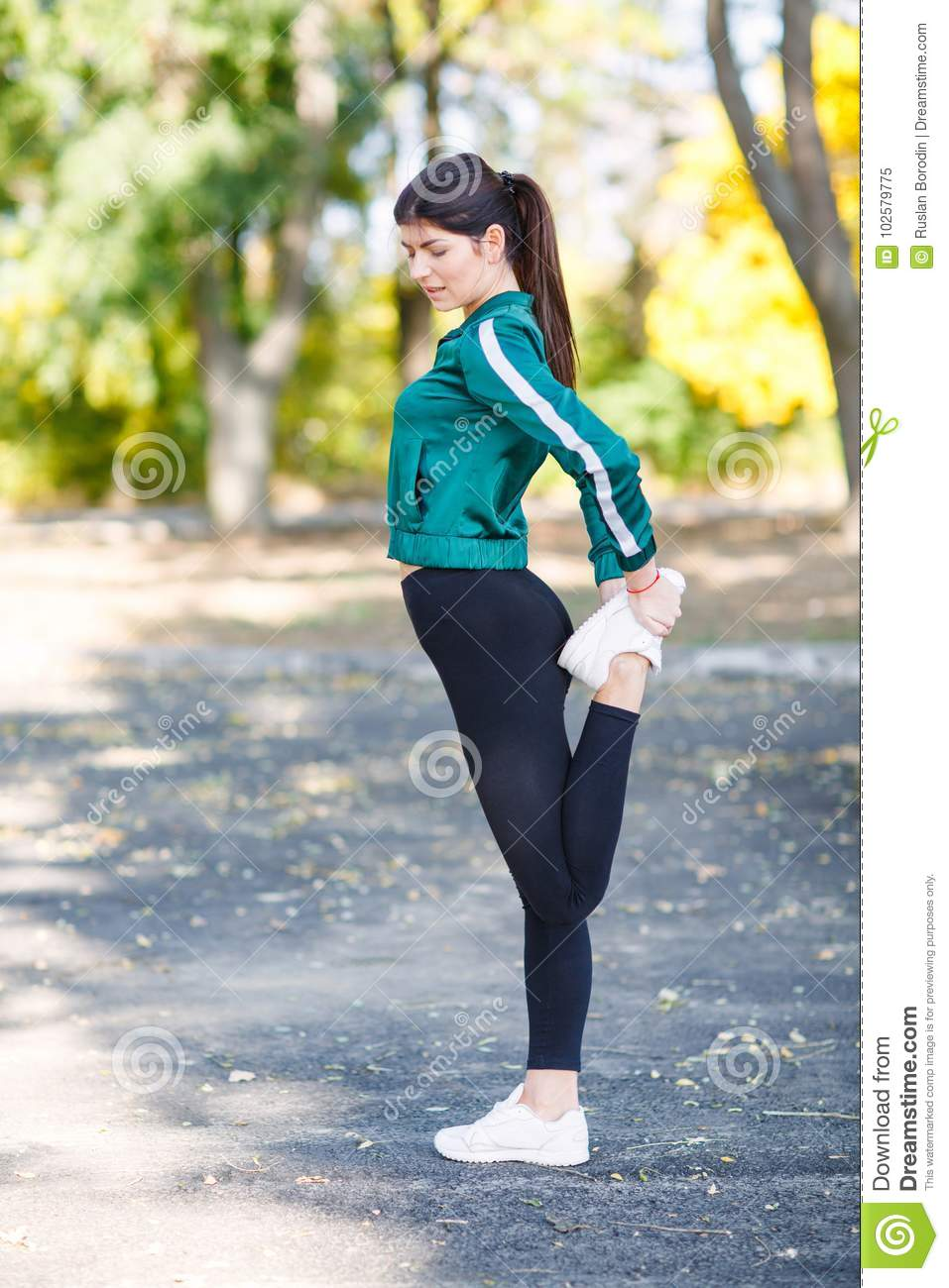A young sporty woman with perfect body doing exercises outdoor.
