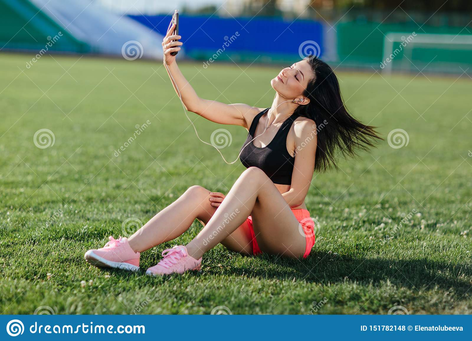 Young sporty joyful woman in sport dress sits on the grass, listens to music in earphones and does selfie-photo on the phone
