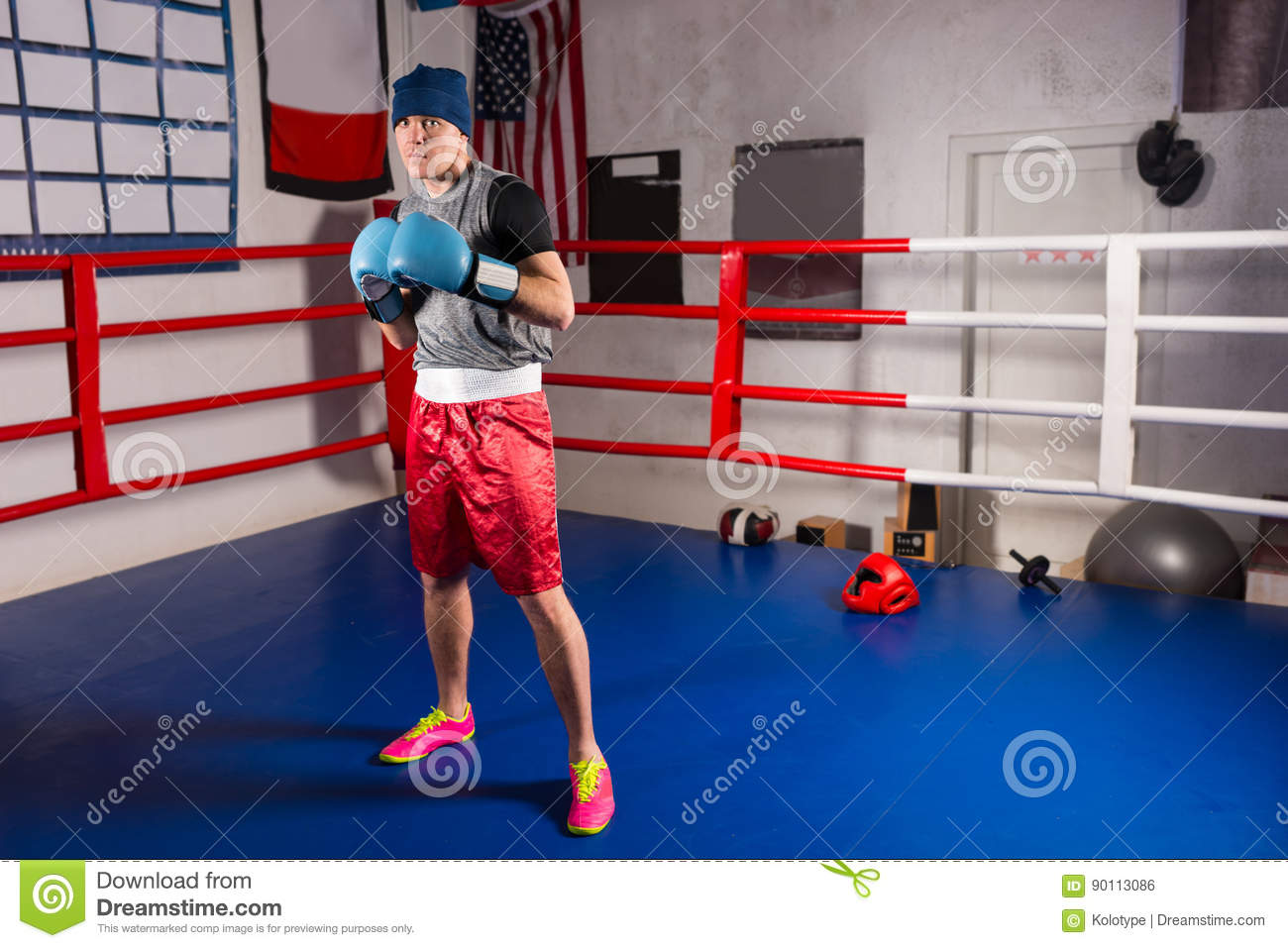 Young sporty male boxer in boxing gloves prepares for battle